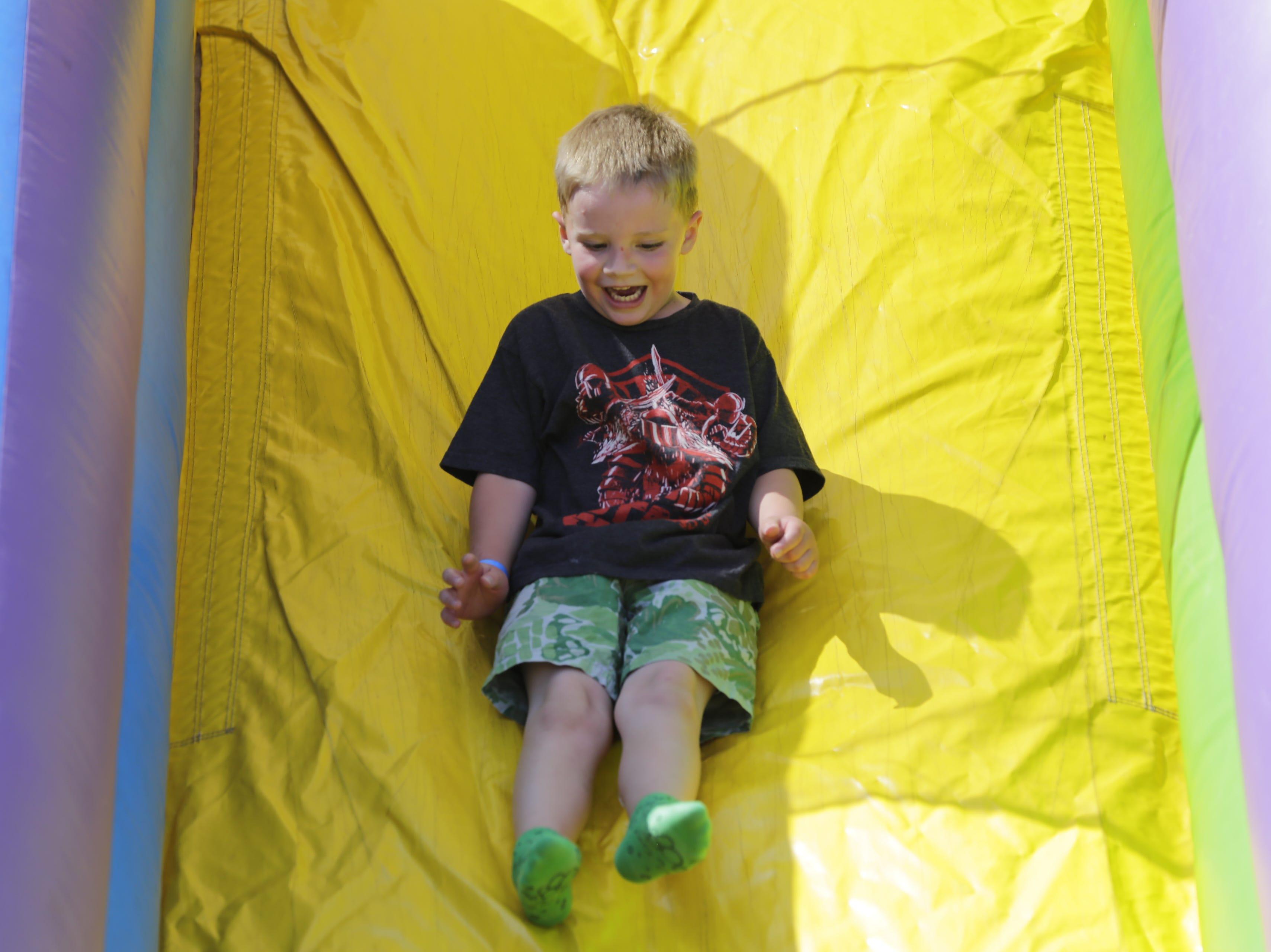 Aidan Kyriss, 6, of Marshfield slides down an inflatable slide at Hub City Days in downtown Marshfield Saturday, July 28, 2018.