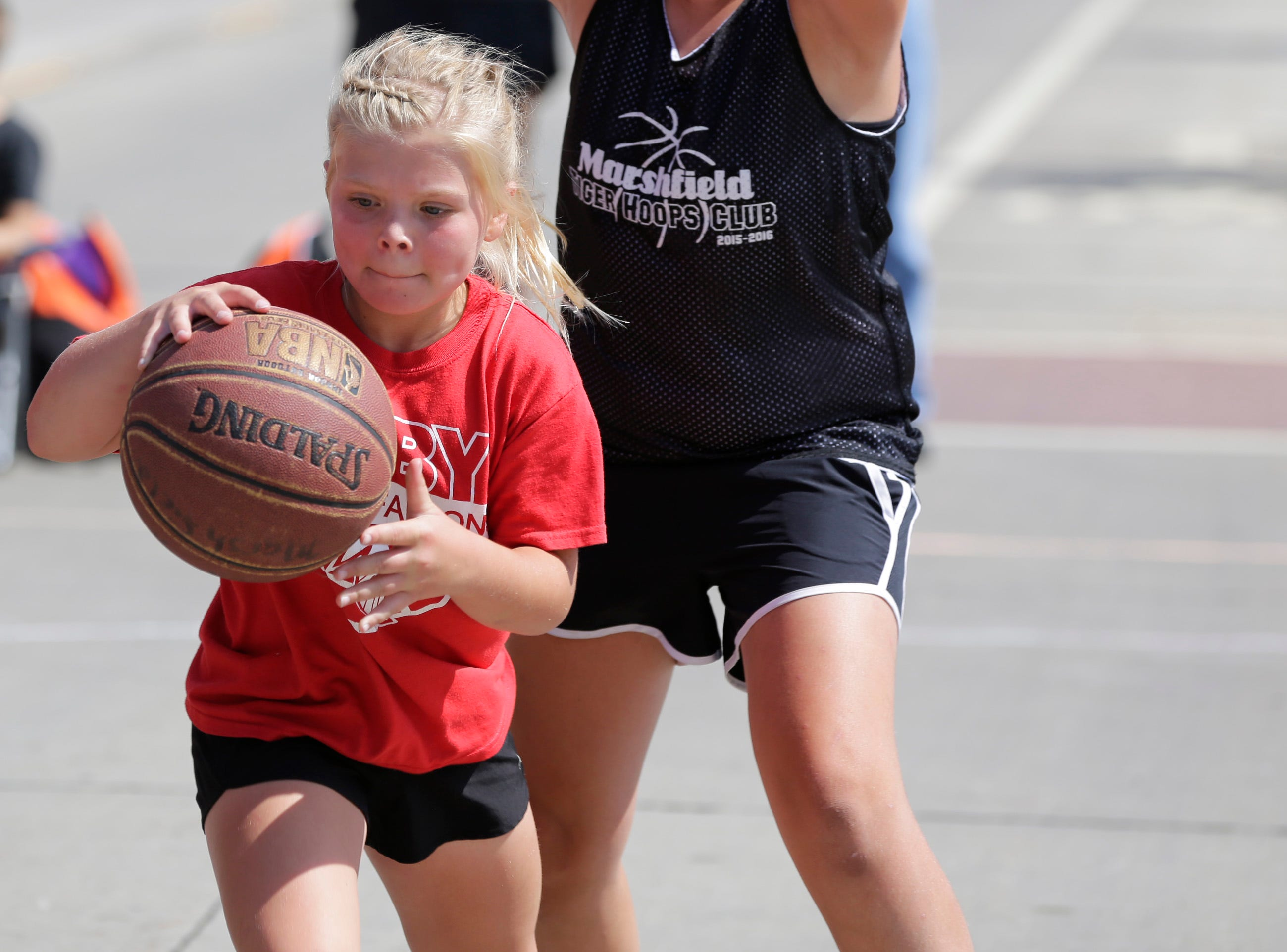 Kendall Rose, 9, from Dorchester, plays in the 3-on-3 basketball tournament during Hub City Days in downtown Marshfield Saturday, July 28, 2018.