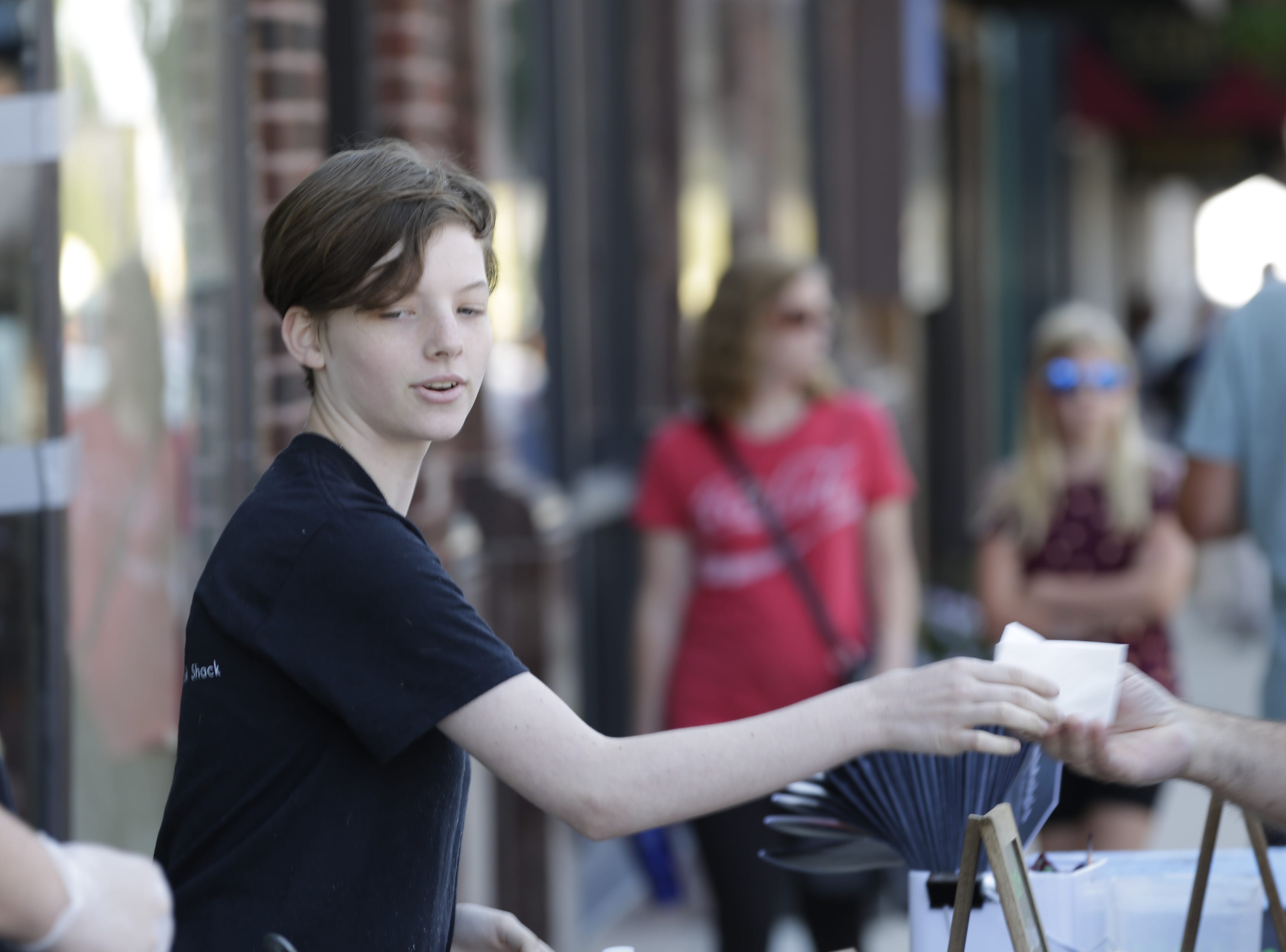 Maddie Olson serves food in front of MoJo's Pasta House and Cajan Cook Shack on Central Avenue at Hub City Days in downtown Marshfield Saturday, July 28, 2018.