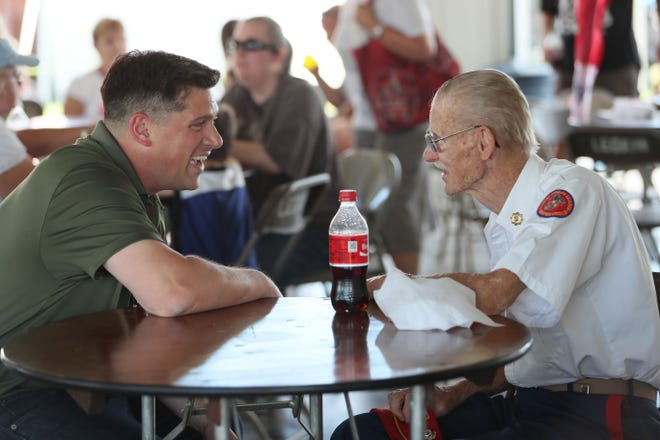 Kevin Nicholson (left) spoke with Carl Heiman of Hubertus, a U.S. Marine Corps veteran, while campaigning in 2018 in the Republican U.S. Senate primary.