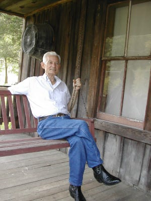Herman Webb, brother of country music star Loretta Lynn, sits on the porch of the home they grew up in at Butcher Hollow, outside Van Lear, Ky., in a file photo dated Oct. 3, 2002.