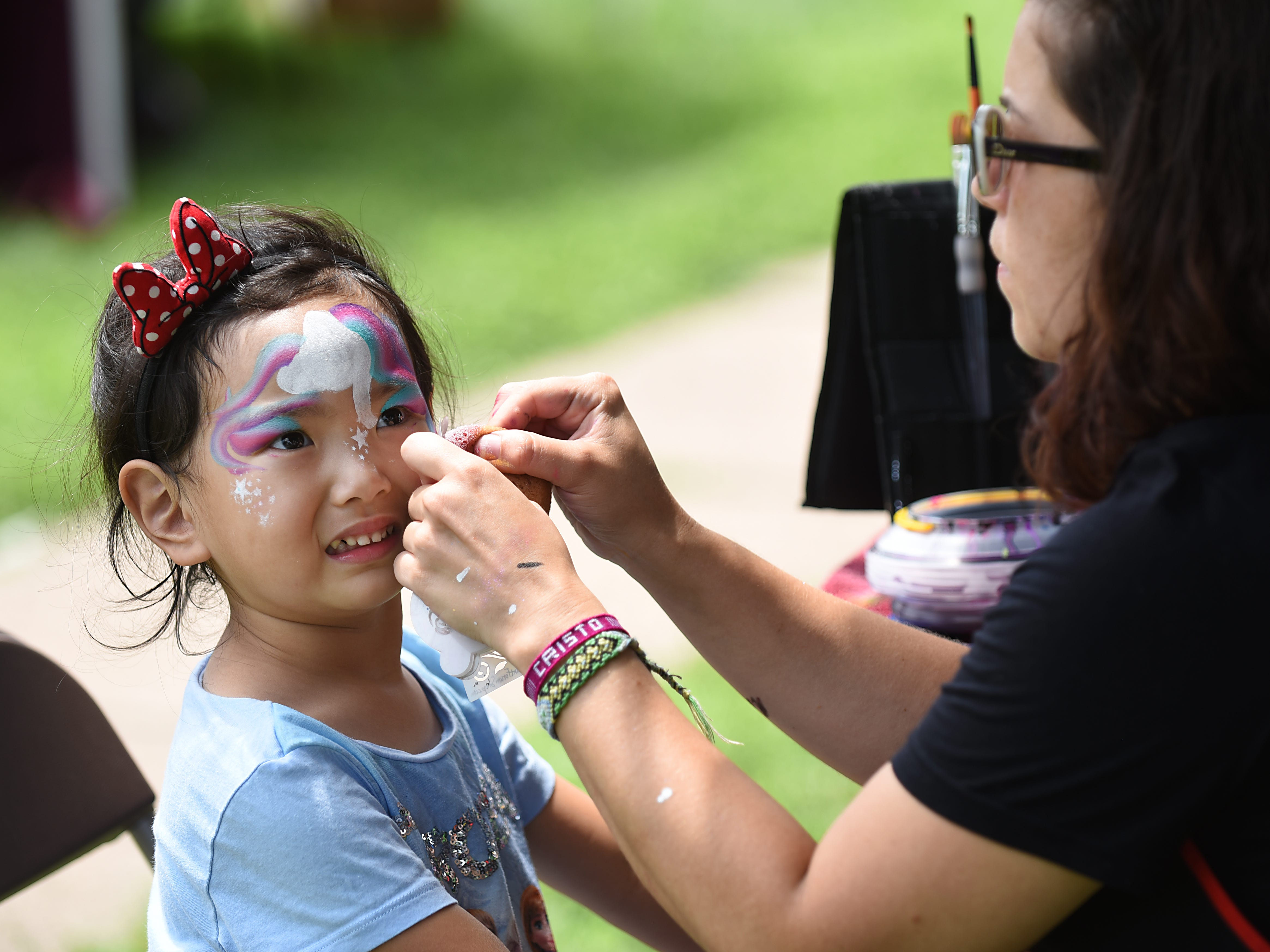 Kaitlyn Wang - four years old from Fort Lee, gets her face painted by Laura Hoyos at the Bergen Family Center tent in the 'Kid Zone' at the Summer-Fest & Sidewalk Sale in Englewood on Saturday July 28, 2018.