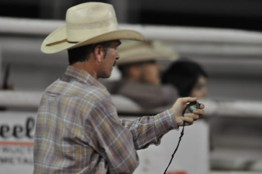 A judge tracks eight seconds at the Eddy County Fair bull riding event July 27.