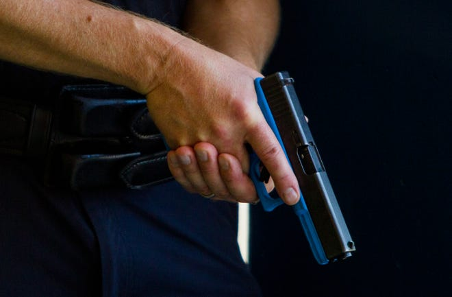 A trainee holds a training gun that does not shoot actual bullets on July 27, 2018, during an Phoenix Police and Fire Department active shooter training at Carl Hayden High School in Phoenix, Arizona.