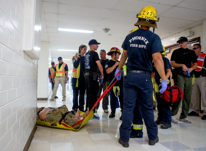 Phoenix Fire department emergency personnel remove injured from the school on July 27, 2018, during an Phoenix Police and Fire Department active shooter training at Carl Hayden High School in Phoenix, Arizona.