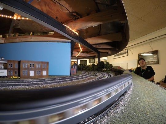A model train streaks by model train operator Zachary Krueger-Brown of Sheboygan during the Sheboygan Society of Scale Model Railroad Engineers summer open house, Saturday, July 28, 2018, in Sheboygan, Wis.