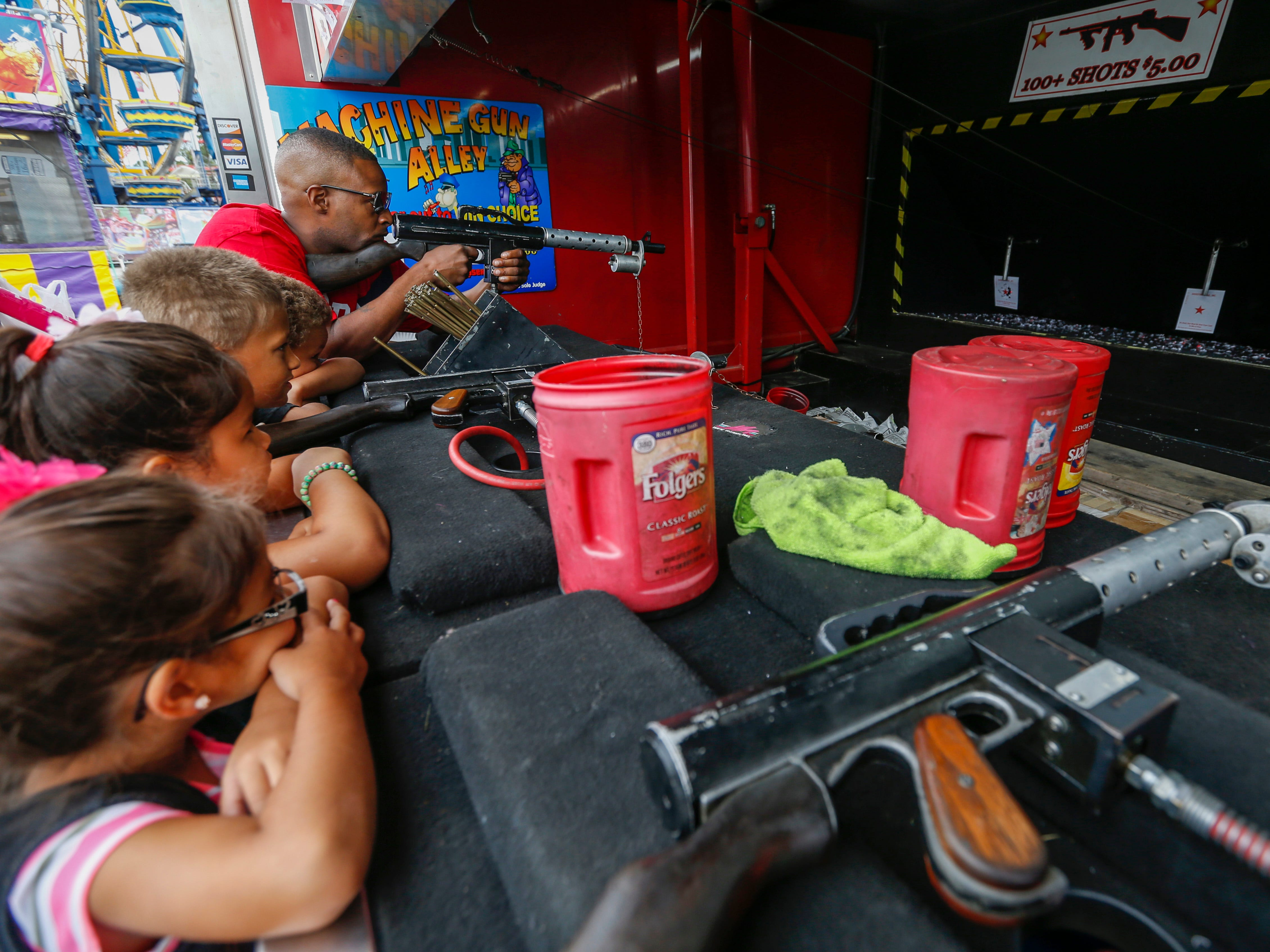 Wesley Box, top right, of Springfield, tries to shoot out the red star as his children, from top, Wes Box, 6, and Michael Box, 8, and nieces Isreal Prescott, 7, and Ariel Prescott, 5, watch at the Ozark Empire Fair on Saturday, July 28, 2018.