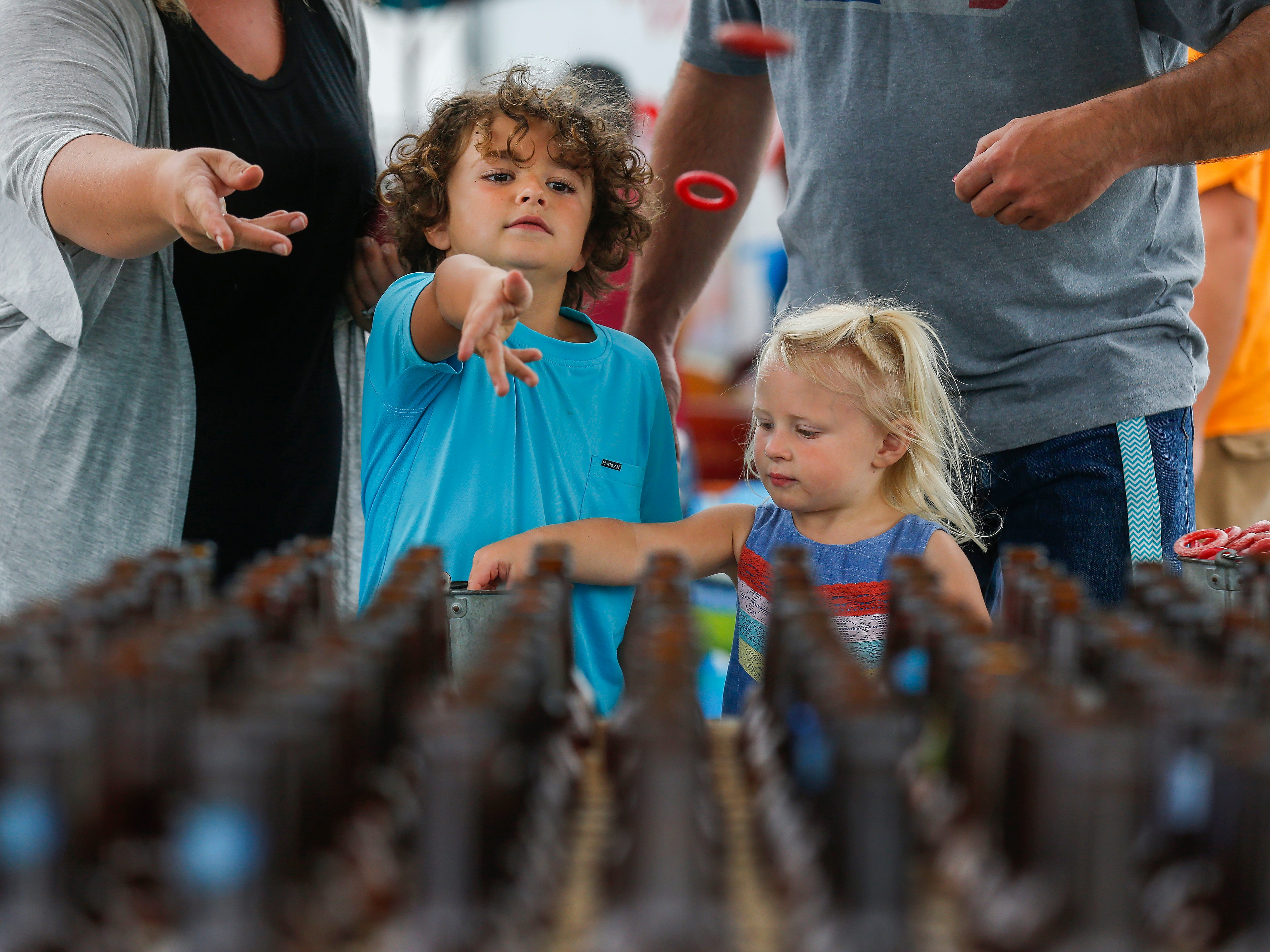 Gatlin Harvey, 5, left, of Mountain View, and his sister Locklynn Harvey, 3, try to toss rings around glass bottles at the Ozark Empire Fair on Saturday, July 28, 2018.