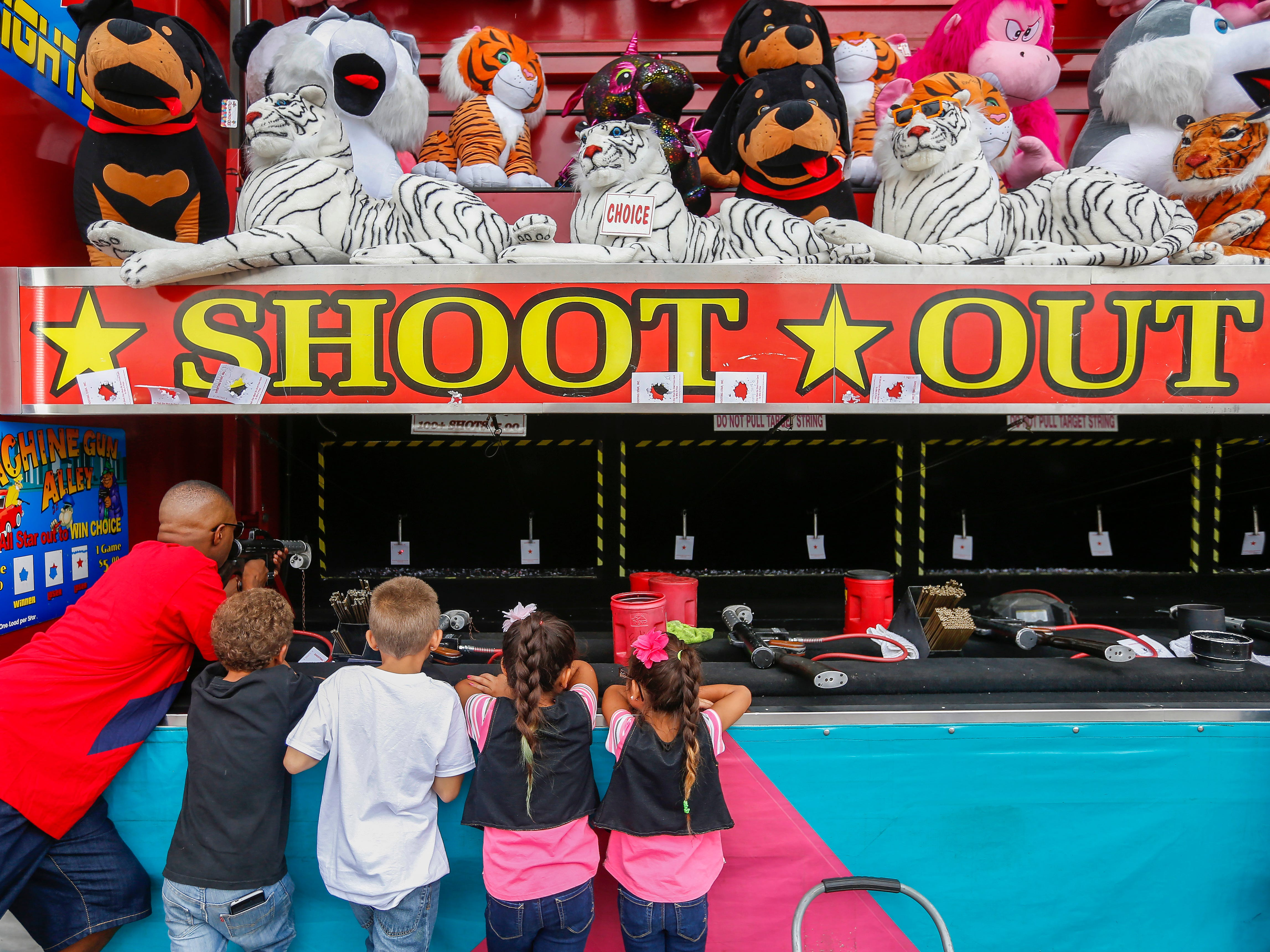 Wesley Box, left, of Springfield, tries to shoot out the red star as his children, from left, Wes Box, 6, Michael Box, 8, and nieces Isreal Prescott, 7, and Ariel Prescott, 5, watch at the Ozark Empire Fair on Saturday, July 28, 2018.