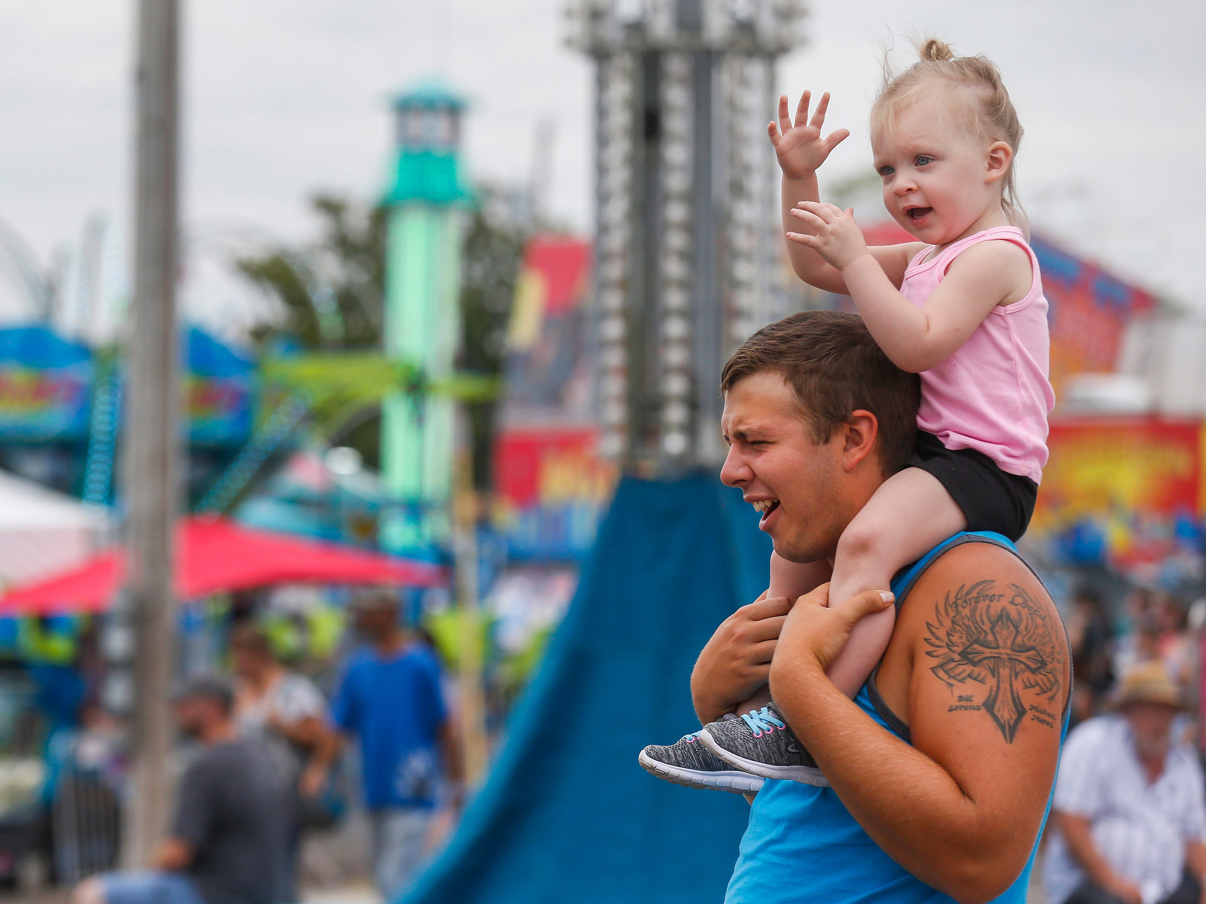 Dakota Lorenz, of Buffalo, reacts as his daughter Callie Barnes, 2, slaps his head at the Ozark Empire Fair on Saturday, July 28, 2018.