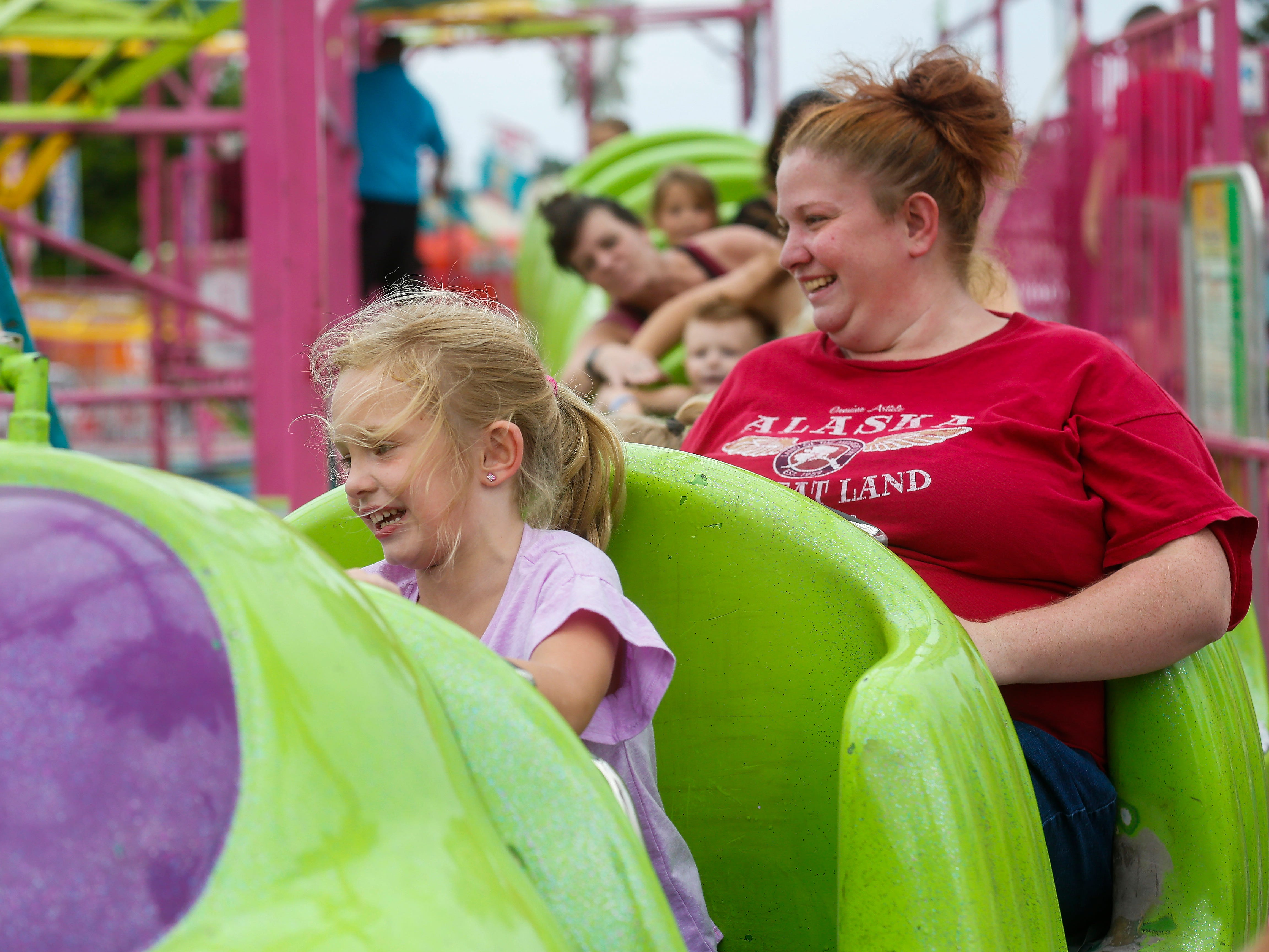 Aeryn Davis, 6, of Columbia, MO., rides the Wacky Worms with her mom Megan Davis at the Ozark Empire Fair on Saturday, July 28, 2018.