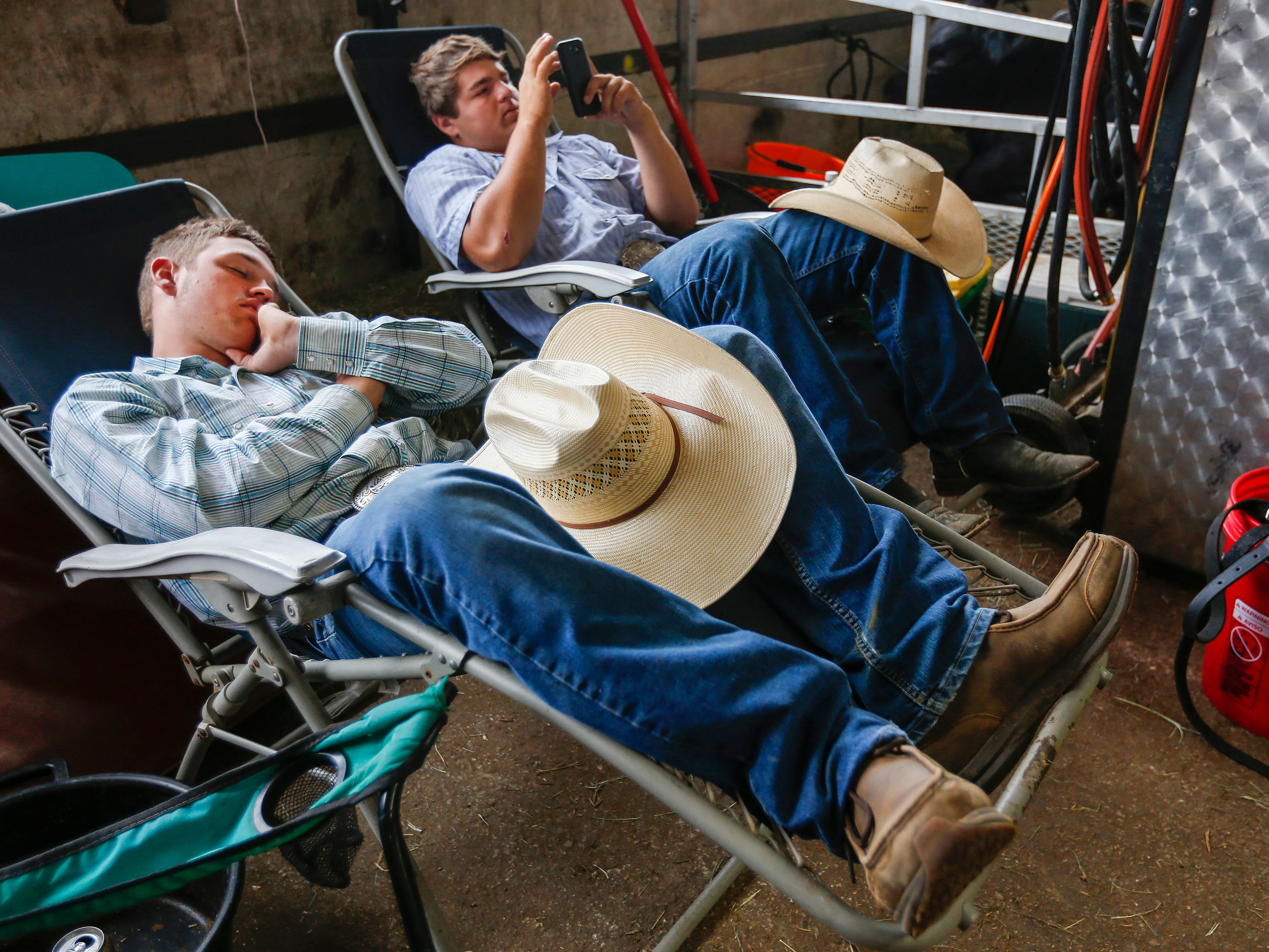 Blaine Bishop, left, Pineville, MO., takes a nap as Colten Leech, of Stark City, MO., looks at his phone at the Ozark Empire Fair on Saturday, July 28, 2018. The two were entered in the Limousin cattle competition.