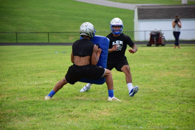 Robert E. Lee senior Kavon Robertson fights past a teammate with a blocking shield during a kickoff coverage drill as the Leemen held their first football practice of the season on Thursday, July 26, 2018, at Robert E. Lee High School. The Leemen open the season Aug. 24 at Turner Ashby.