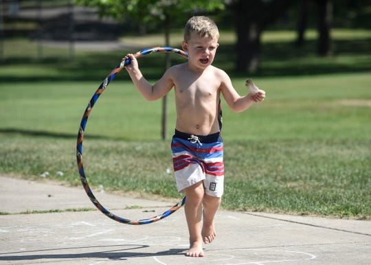 Gavin Tinklenberg carries his new hula hoop Saturday, July 28, at Wilson Park in St. Cloud.