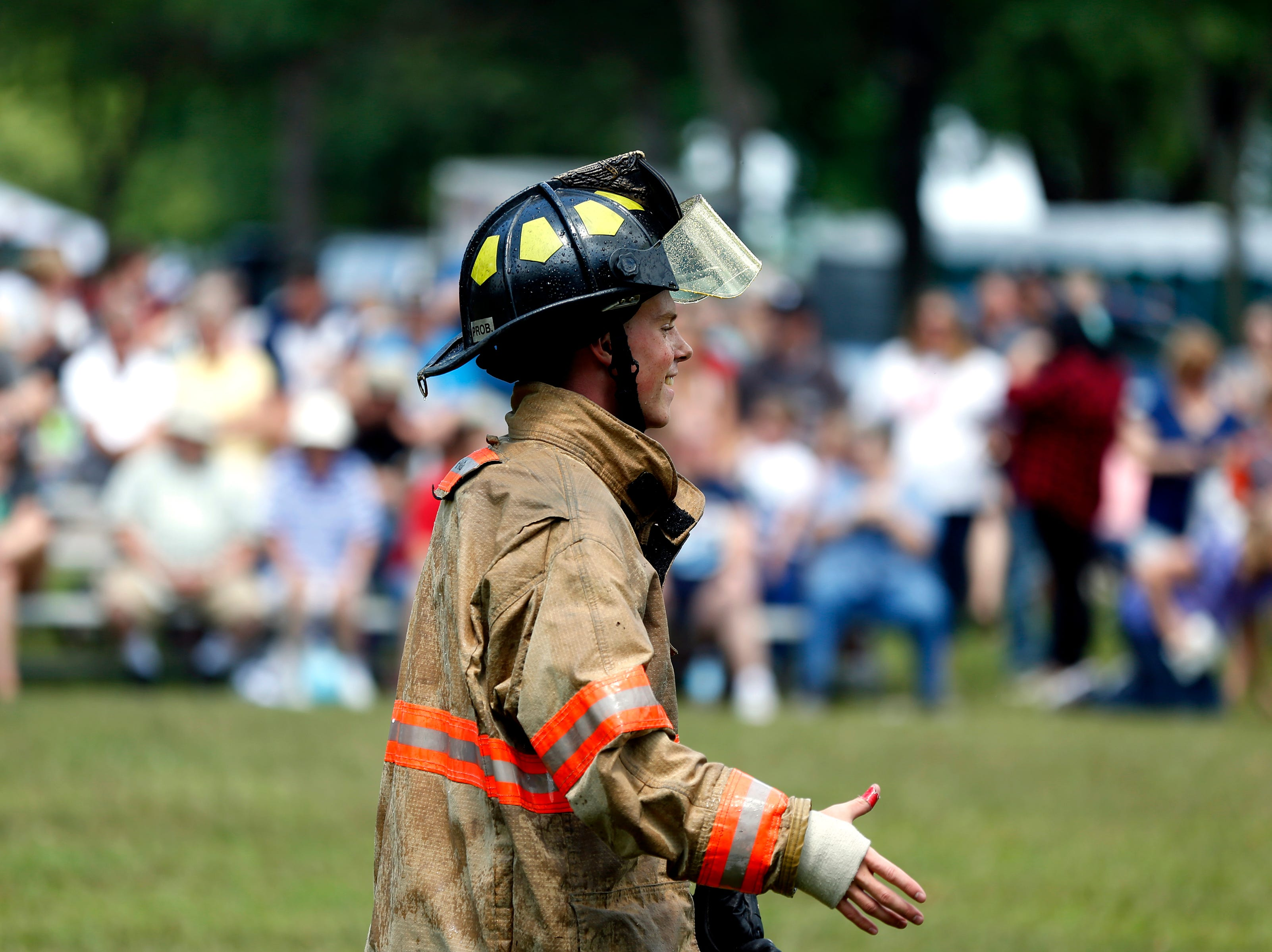 A firefighter prepares to shake hands with opponents during the water fights during Celebrate Plover at Lake Pacawa Park in Plover, Wis., July 28, 2018.