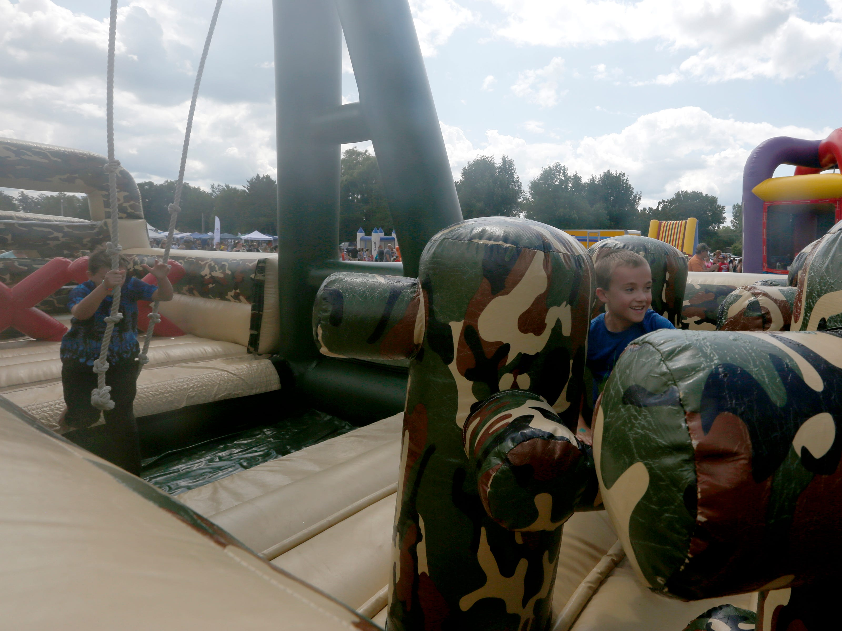 Kids play on an inflatable obstacle course during Celebrate Plover at Lake Pacawa Park in Plover, Wis., July 28, 2018.