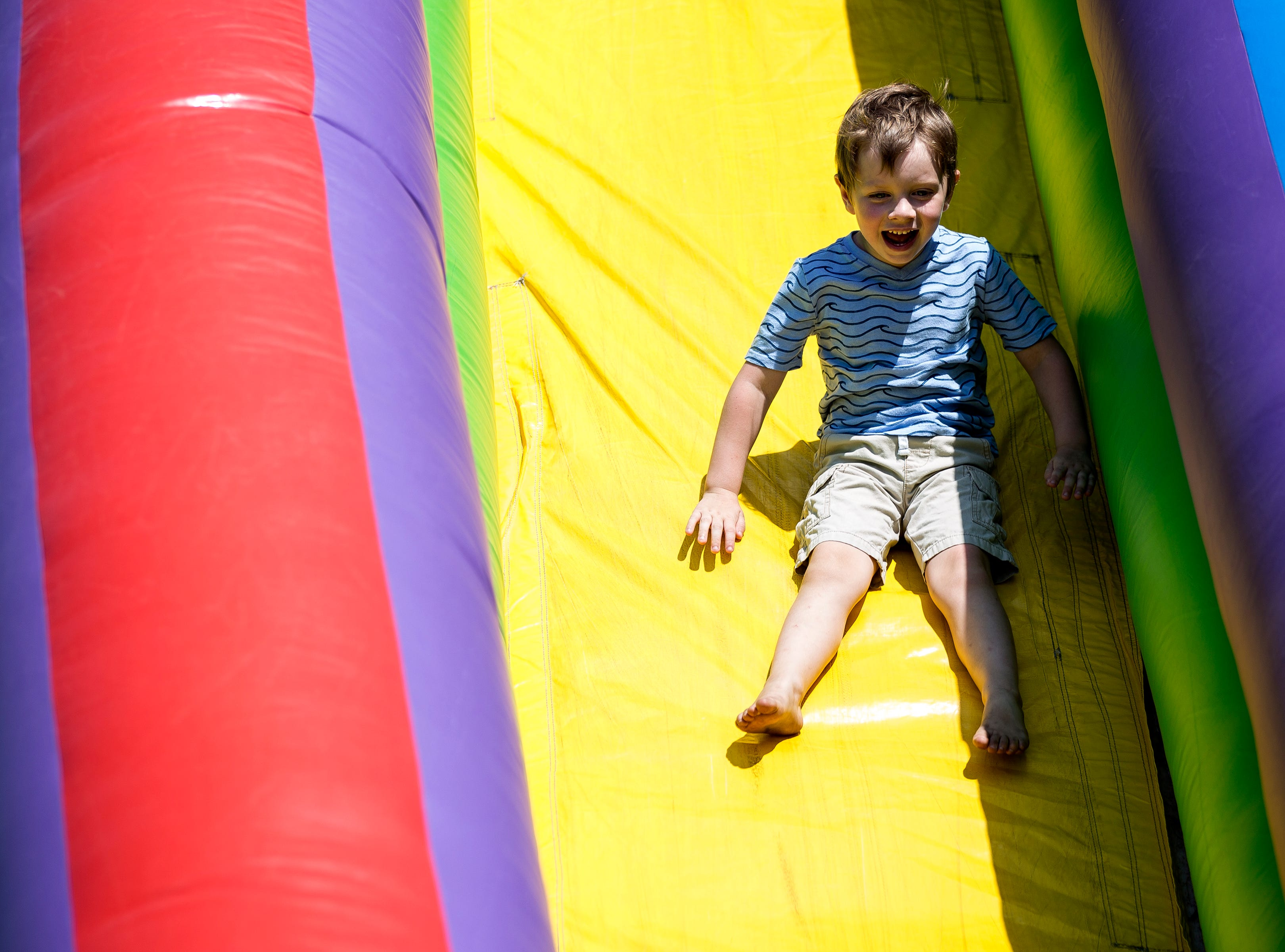 A boy rides down an inflatable slide during Celebrate Plover at Lake Pacawa Park in Plover, Wis., July 28, 2018.