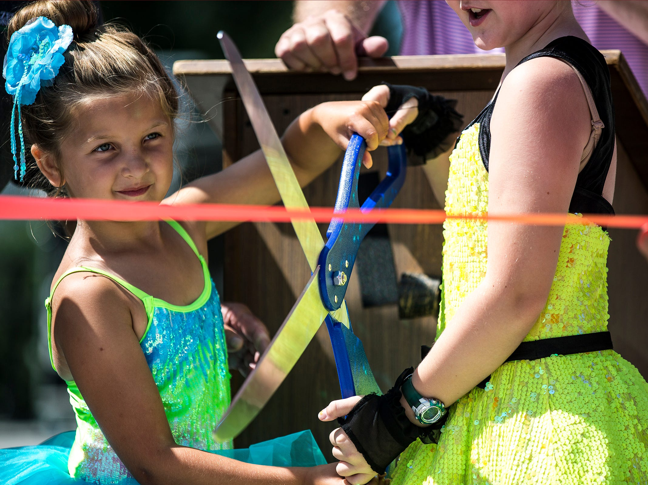 Members of the Dance Dynamics prepare to cut the ribbon during a ceremony for the new Band Shell at Lake Pacawa during Celebrate Plover at Lake Pacawa Park in Plover, Wis., July 28, 2018.