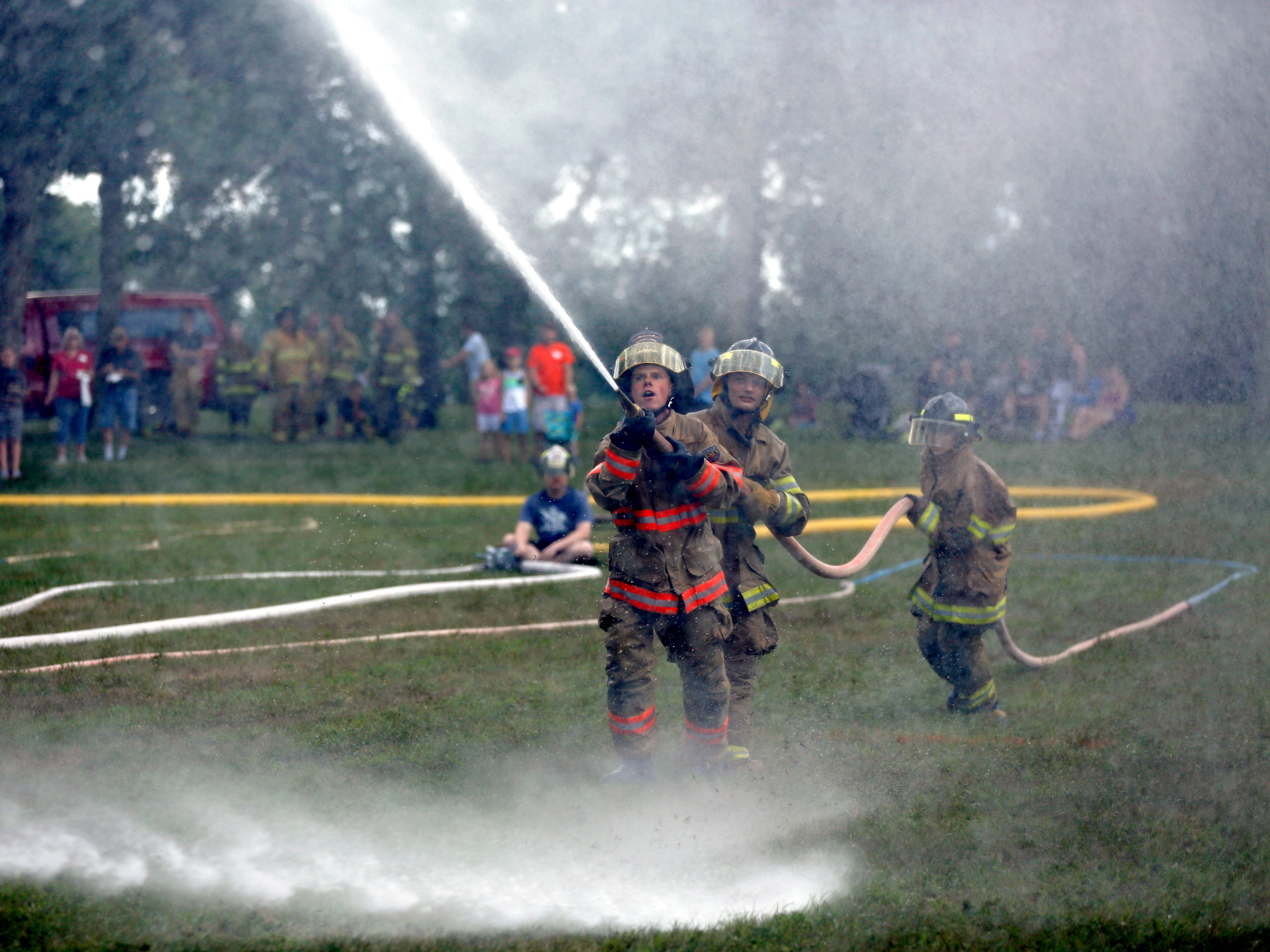 Firefighters participate in the water fights during Celebrate Plover at Lake Pacawa Park in Plover, Wis., July 28, 2018.
