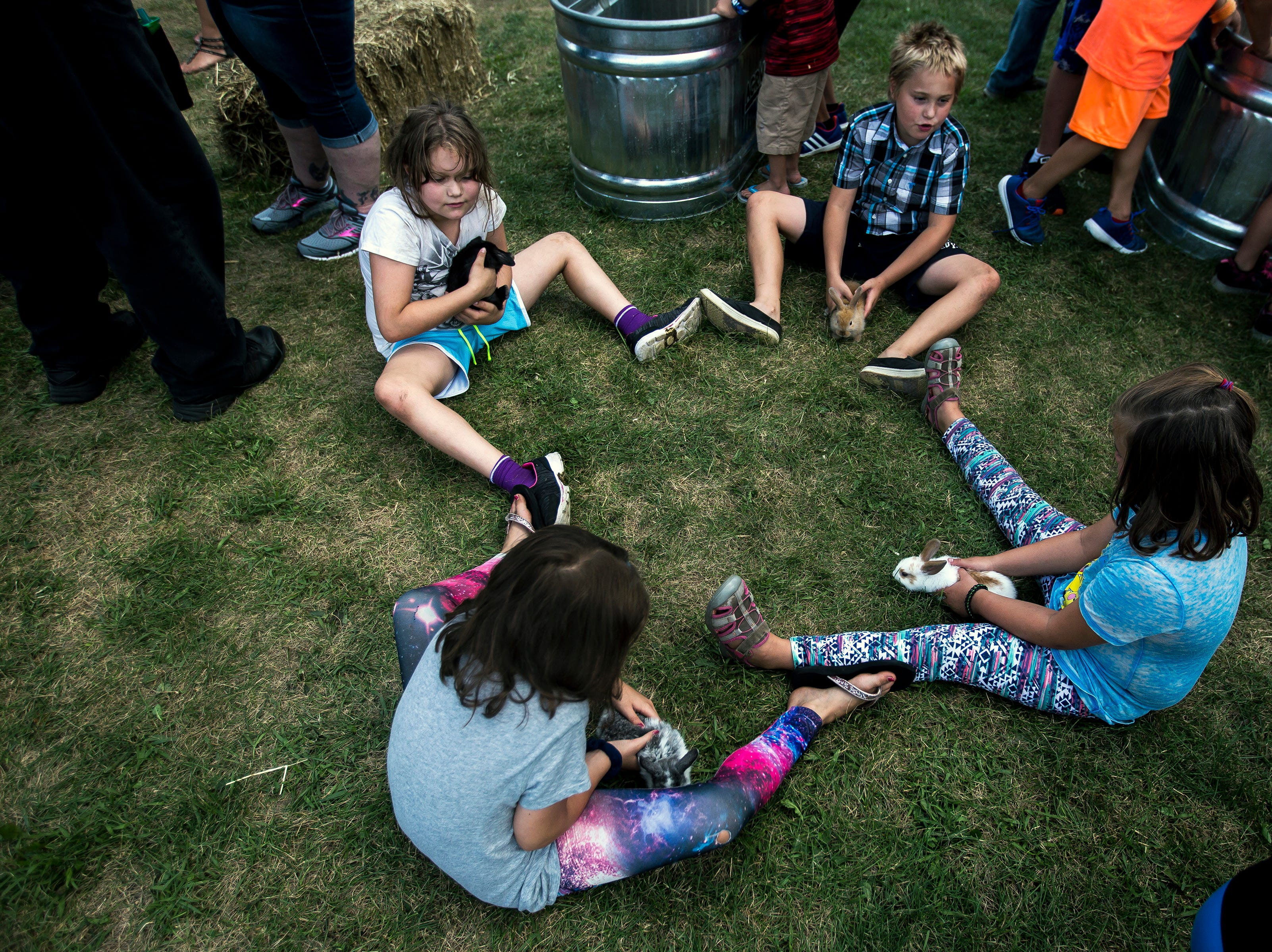 Kids pet and hold rabbits at a petting zoo during Celebrate Plover at Lake Pacawa Park in Plover, Wis., July 28, 2018.