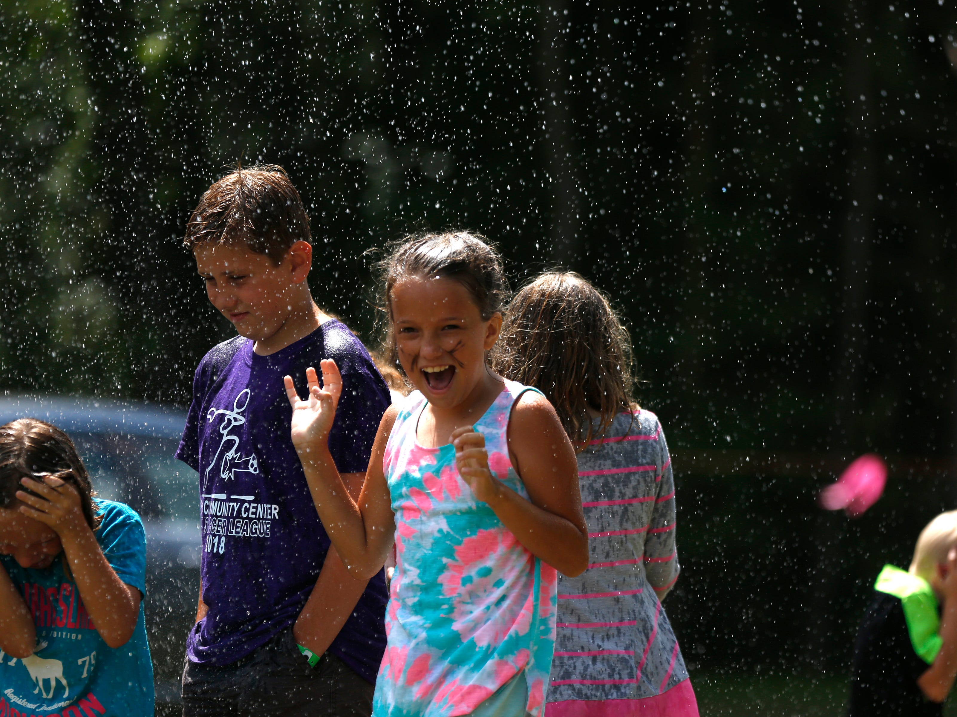 Kids play in water sprayed during the fire department water fights during Celebrate Plover at Lake Pacawa Park in Plover, Wis., July 28, 2018.