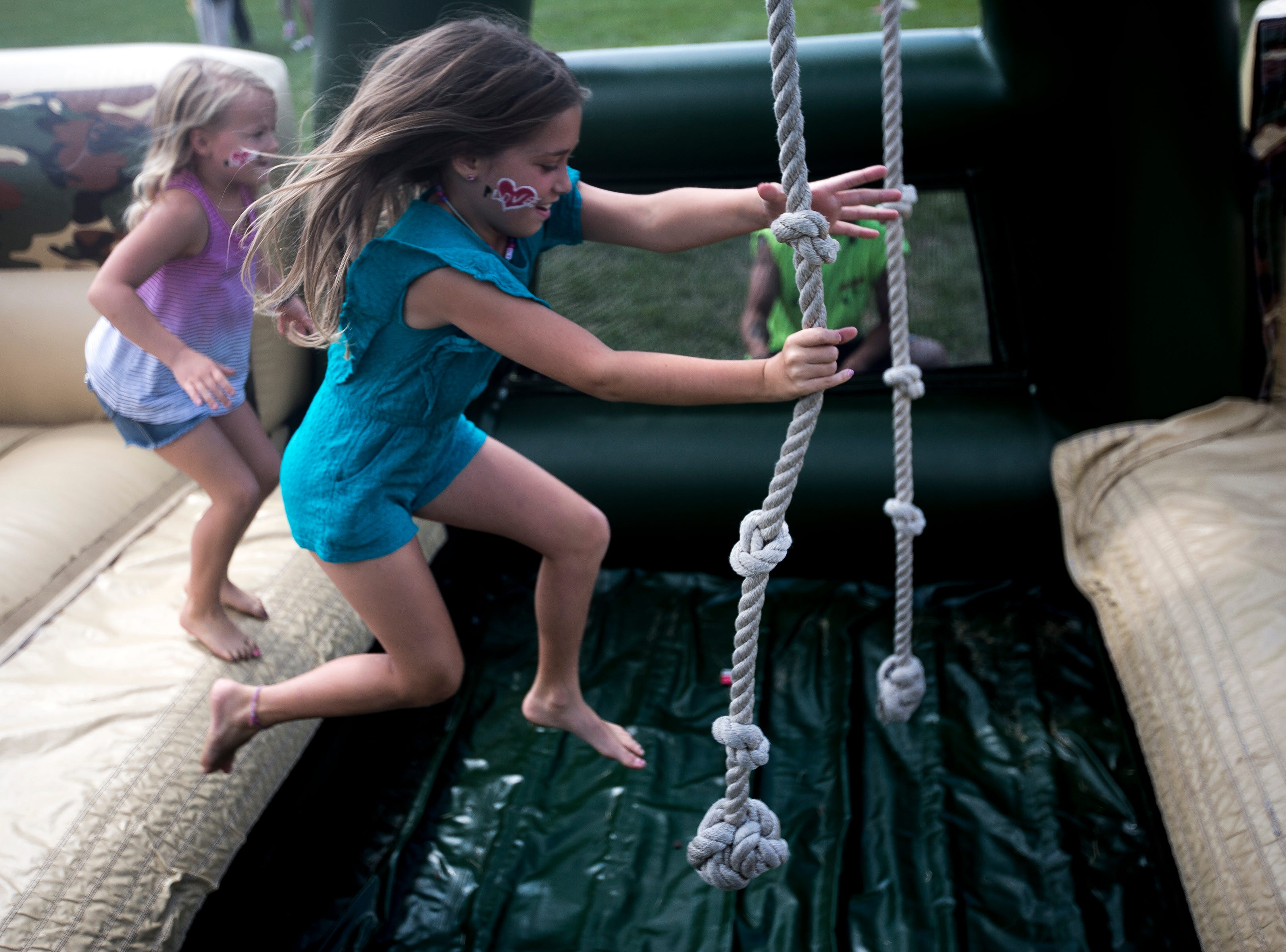 Girls play on an inflatable obstacle course during Celebrate Plover at Lake Pacawa Park in Plover, Wis., July 28, 2018.