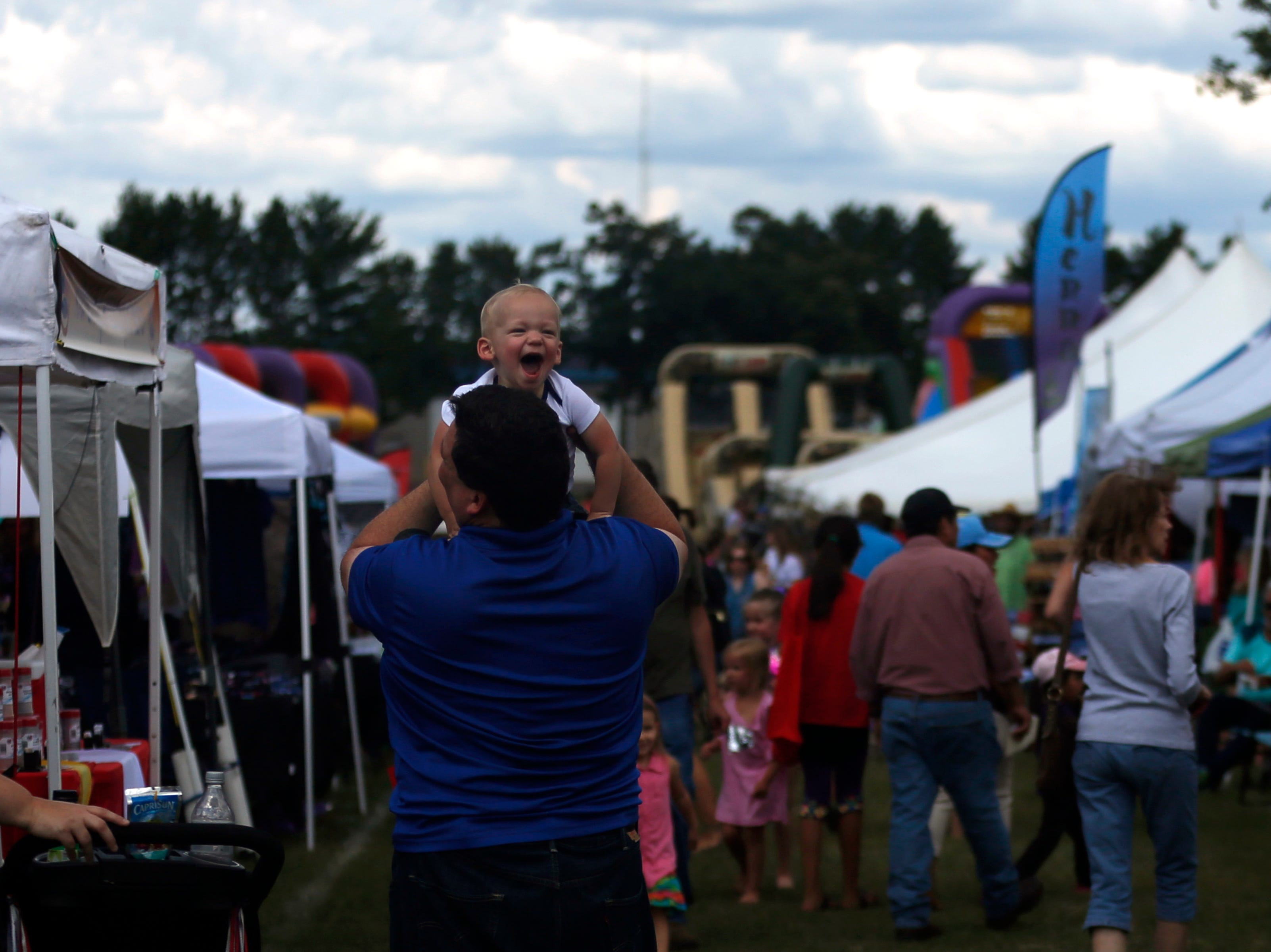 A baby laughs while being played with during Celebrate Plover at Lake Pacawa Park in Plover, Wis., July 28, 2018.