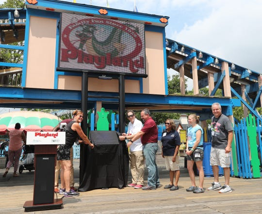 Deputy Westchester County Executive Ken Jenkins, rear left, and Parks Commissioner Kathleen O'Connor, left, prepare to unveil the plaque from American Coaster Enthusiasts designating the Kiddy Coaster landmark status at Playland Park in Rye on Saturday.