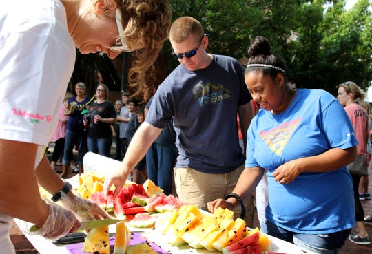 People pick out slices of watermelon at Watermelon Day Saturday, July 28, 2018, at the downtown Wichita Falls Farmers Market.