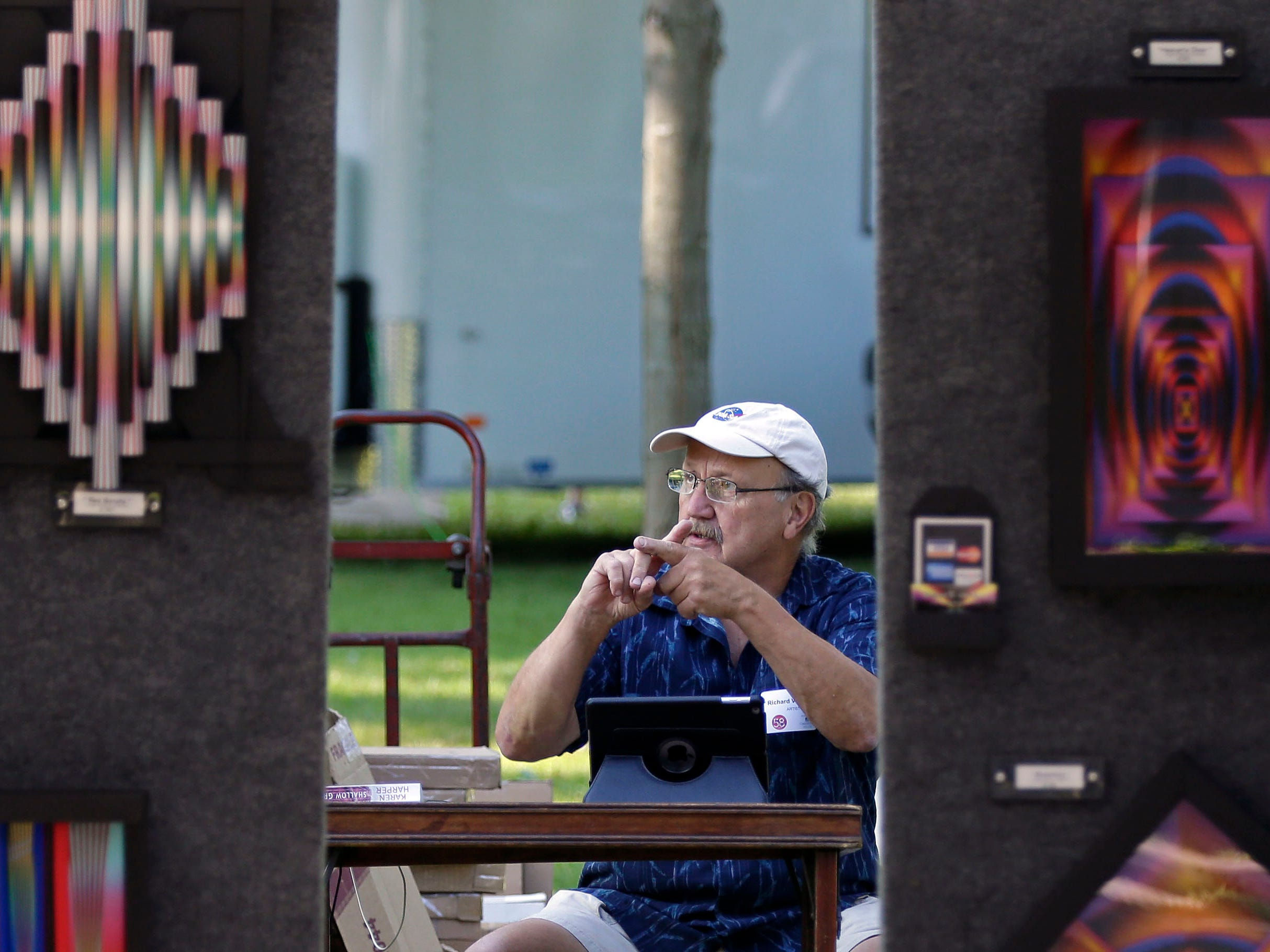 An artist works at his iPad before the 58th annual Art at the Park takes place Sunday, July 29, 2018, at City Park in Appleton, Wis.Ron Page/USA TODAY NETWORK-Wisconsin