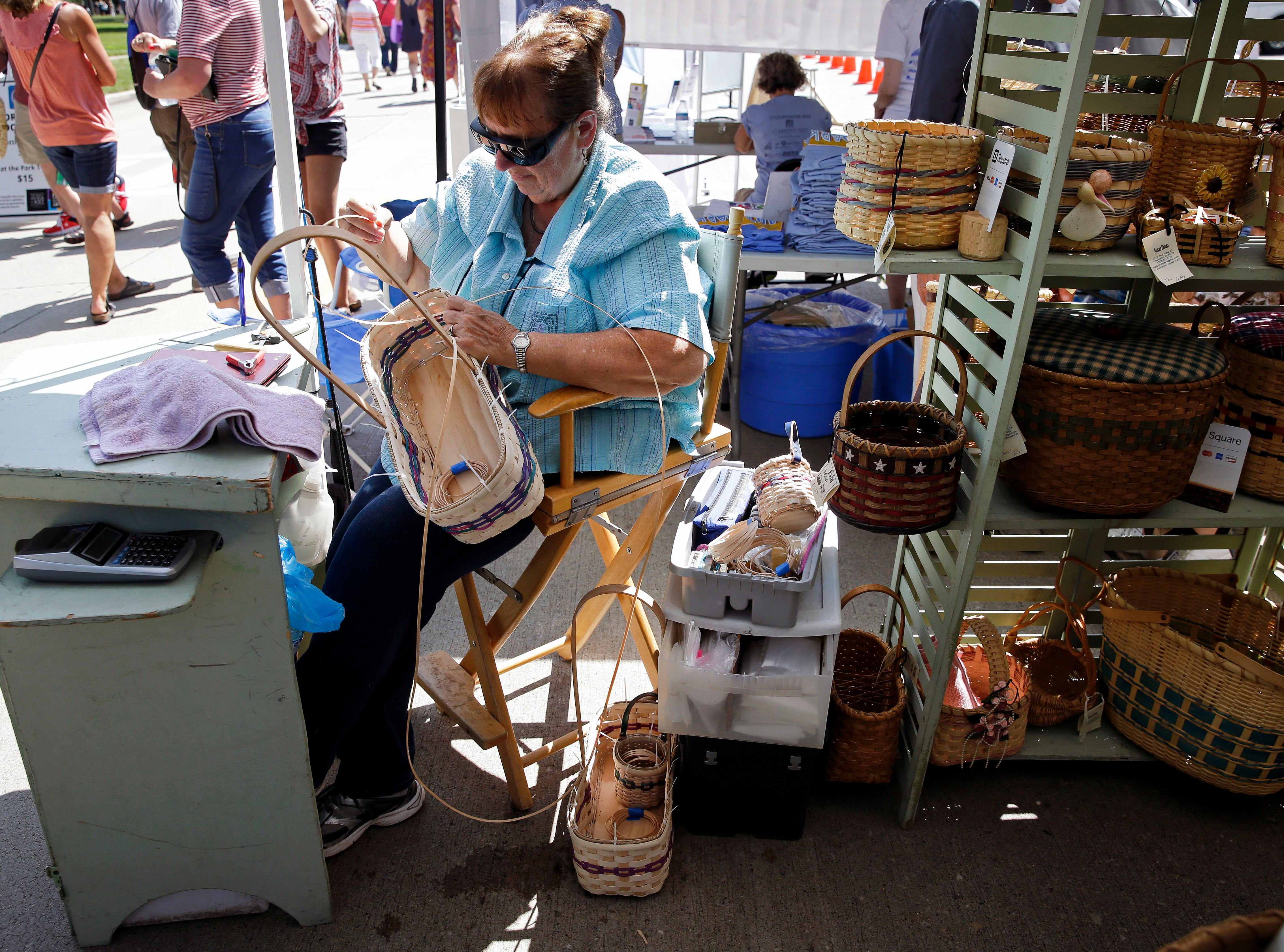 Susan Preuss weaves a basket at her booth as the 58th annual Art at the Park takes place Sunday, July 29, 2018, at City Park in Appleton, Wis.Ron Page/USA TODAY NETWORK-Wisconsin