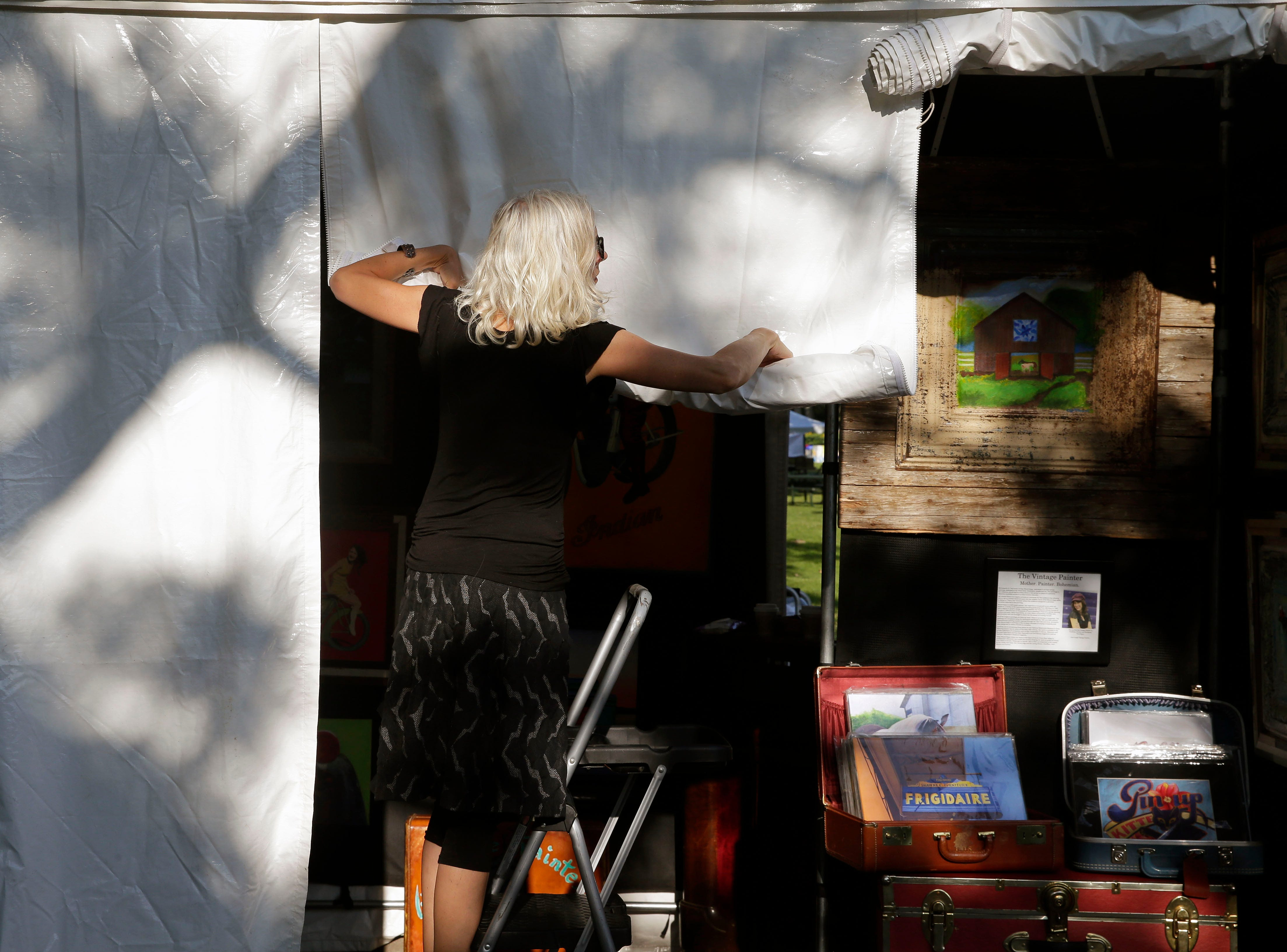 Chrissy Mount gets her booth ready to open as the 58th annual Art at the Park takes place Sunday, July 29, 2018, at City Park in Appleton, Wis.Ron Page/USA TODAY NETWORK-Wisconsin