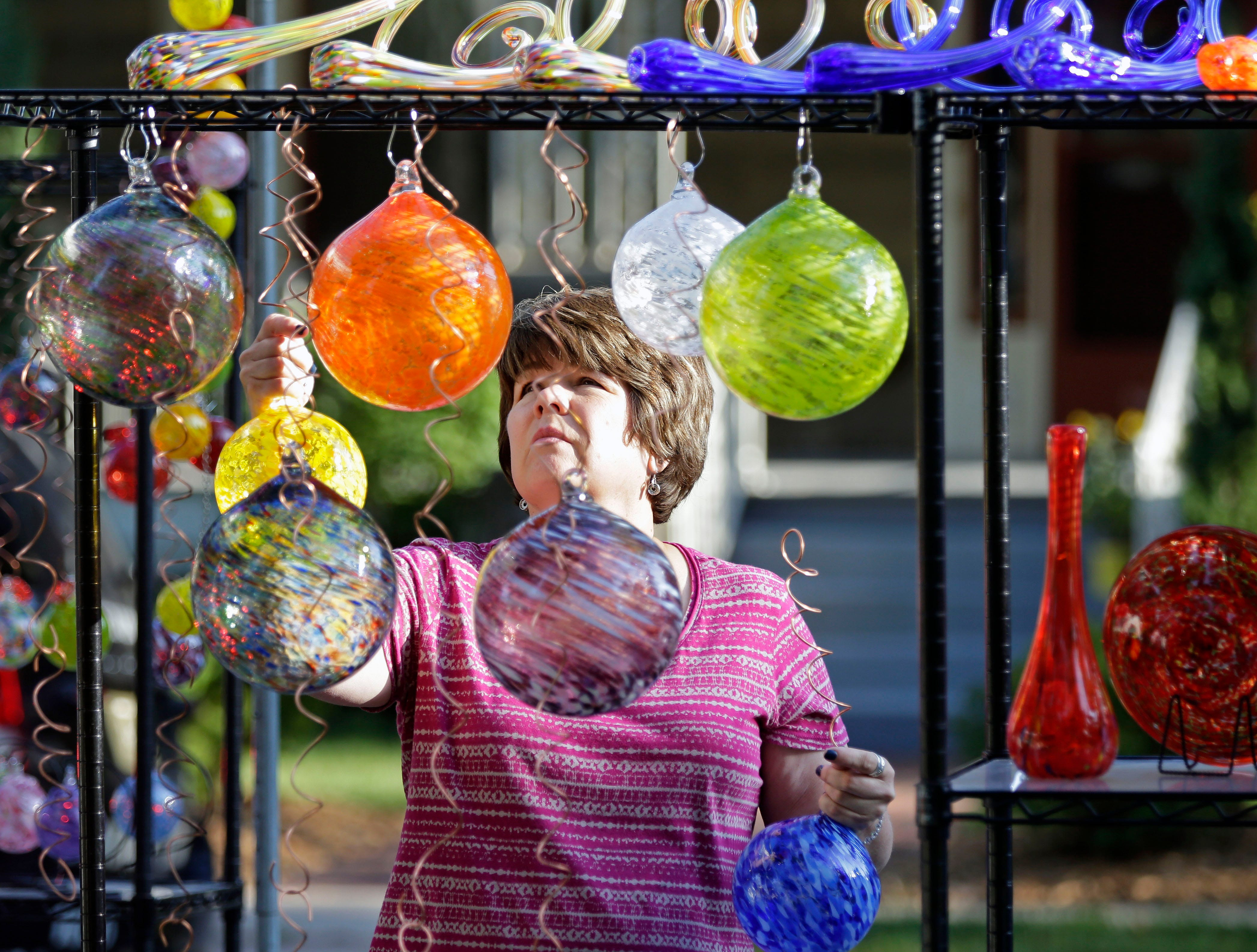 Deb Fenn of Decorah, Iowa gets her booth ready for visitors as the 58th annual Art at the Park takes place Sunday, July 29, 2018, at City Park in Appleton, Wis.Ron Page/USA TODAY NETWORK-Wisconsin