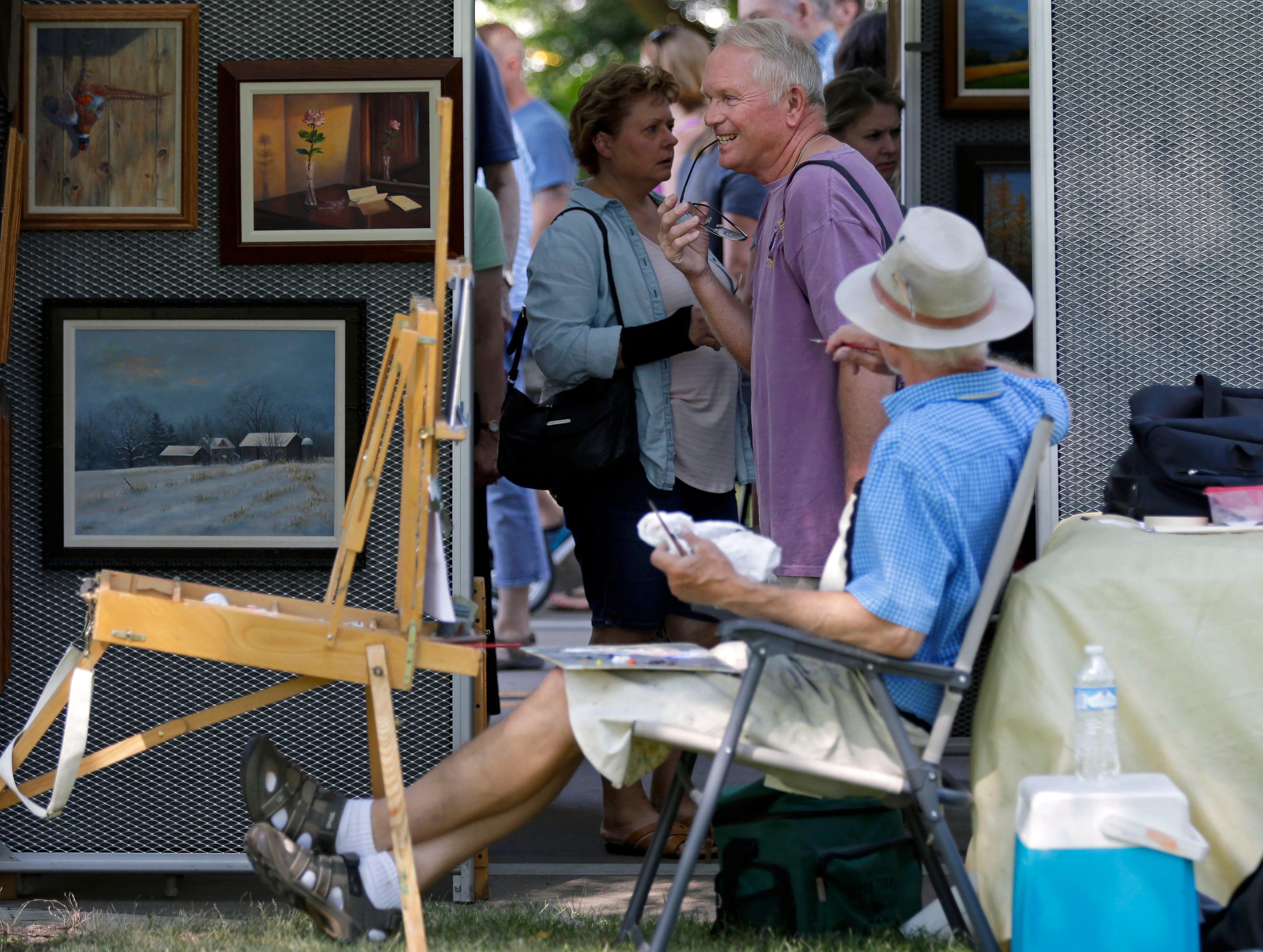 Greg Hartel visits with artist Bill Millonig as the 58th annual Art at the Park takes place Sunday, July 29, 2018, at City Park in Appleton, Wis.Ron Page/USA TODAY NETWORK-Wisconsin