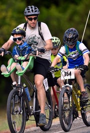 Brandon Rogers coaches his son Bennett, 8, while balancing his 3-year-old son Quinn and towing his 5-year-old son Lucas during the final leg of the 11-mile course of the Tour de Gap Saturday.