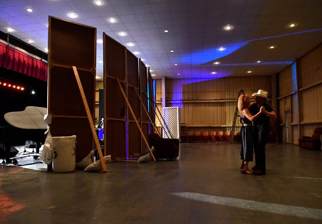 Mark Wayne Hagood and Becky Stokes dance behind the onstage partitions during the C-City Opry on July 19 in Colorado City. The musical show is the third Thursday of every month in the city's 1899 opera house.