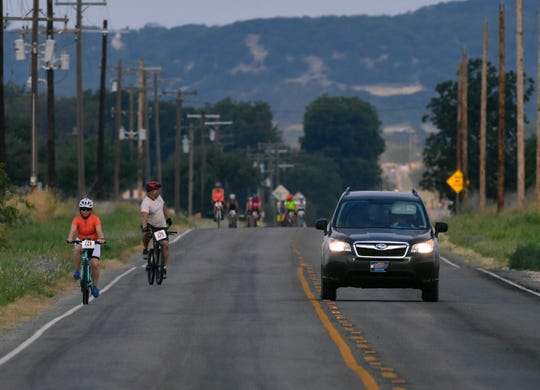 A motorists pulls into the opposing lane on Lemons Gap Road as the driver passes competitors in the 27-mile course of the Tour de Gap bicycle race.