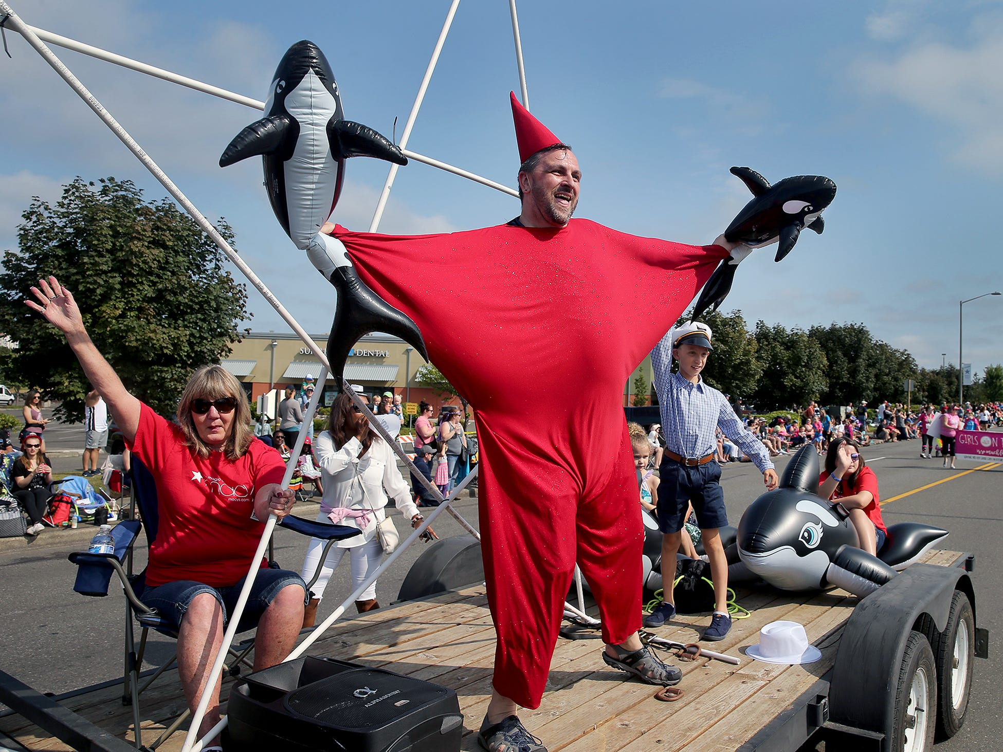 Jay Clayton, of Macy's at the Silverdale Mall, dances with Orcas on their float during the Whaling Days Festival Parade along Silverdale Way in Silverdale, WA on Saturday, July 28, 2018.