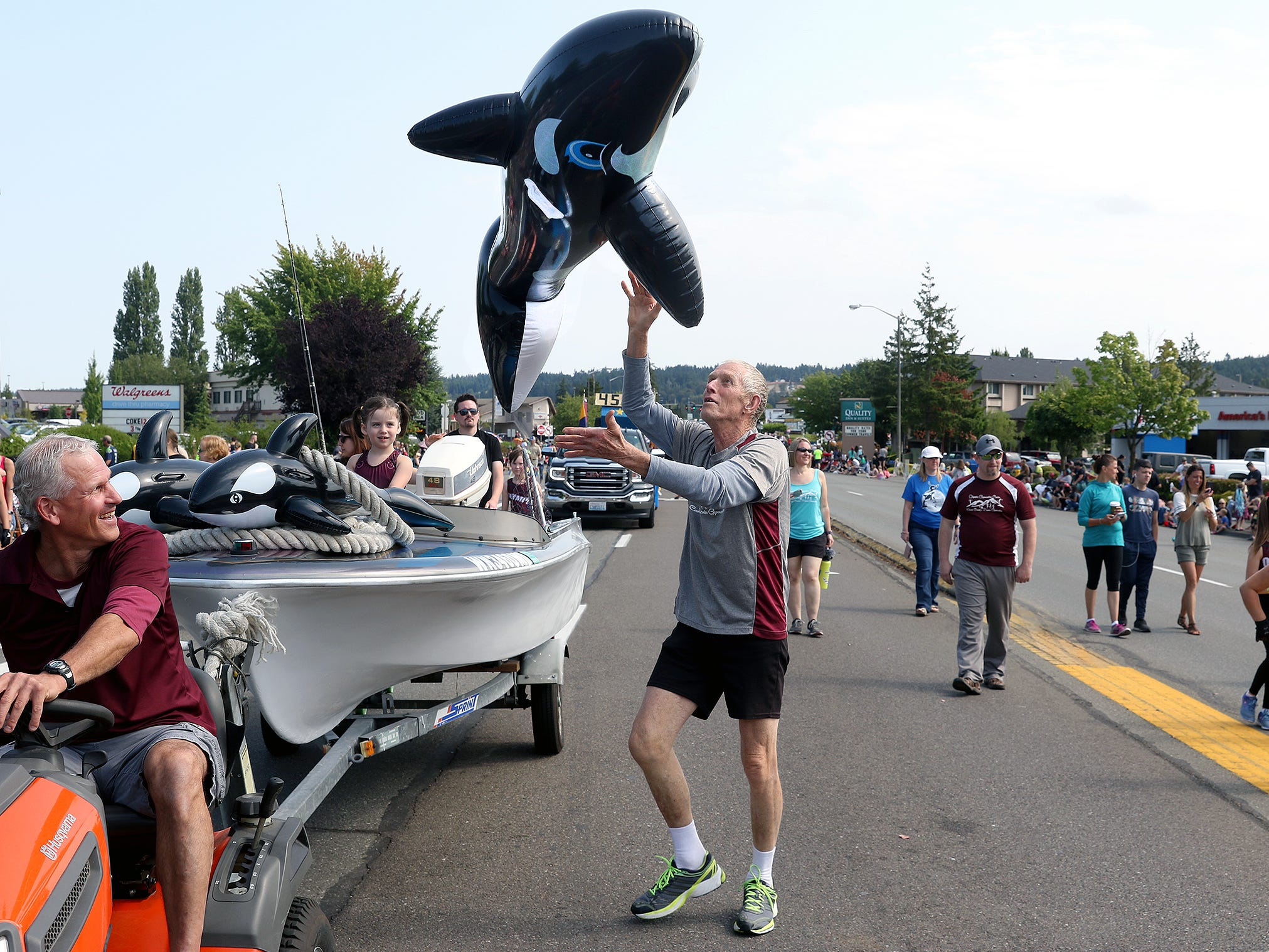 Coach Bob Cummins of the Olympic Gymnastics Center in Silverdale tosses an orca whale while taking part in the Whaling Days Festival Parade along Silverdale Way in Silverdale, WA on Saturday, July 28, 2018.