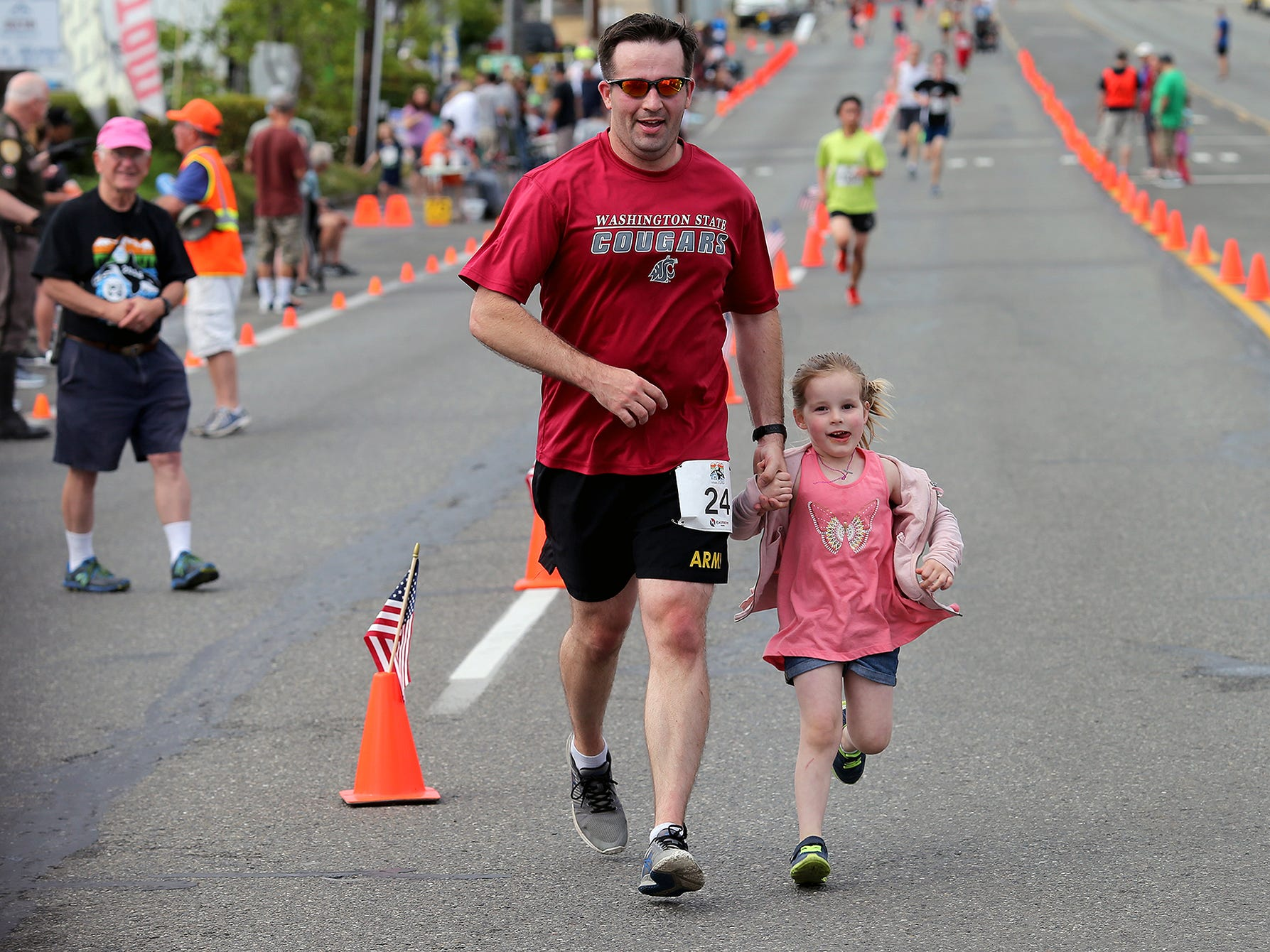 Adam Cates, of Bremerton, and his daughter Stella, 4, run during the 1 mile run walk at the Whale of a Run to the finish line on Silverdale Way in Silverdale, WA on Saturday, July 28, 2018.