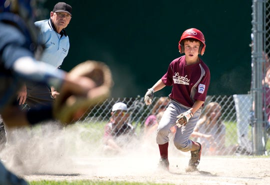 Lyndon's Austin Strang, right, scores in the fourth inning of Sunday's decisive Little League baseball championship game at Schifilliti Field.
