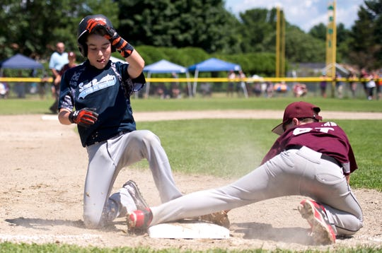 South Burlington's Kevin Dowling slides safely into third during Sunday's decisive Little League baseball championship game at Schifilliti Field.