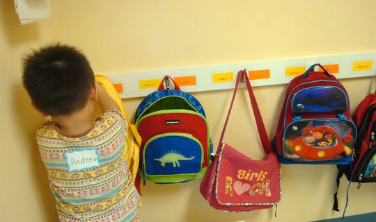 Andrew Chung hangs up his backpack during the first day of school in 2009 for the 3-year-olds at the Montessori Academy of Cincinnati.