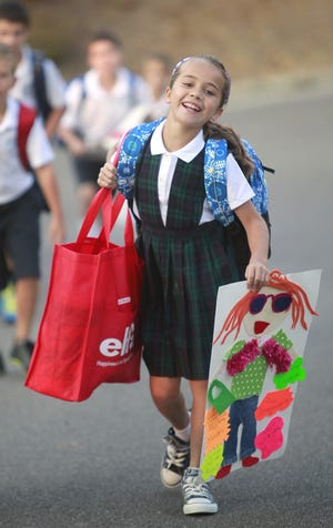"Third-grader Madeline Hines carries in a self-portrait on the first day of school at Cardinal Pacelli School in Mount Lookout in 2012. The kids walked into the school on a ""red carpet"" as some teachers and the principal greeted them."