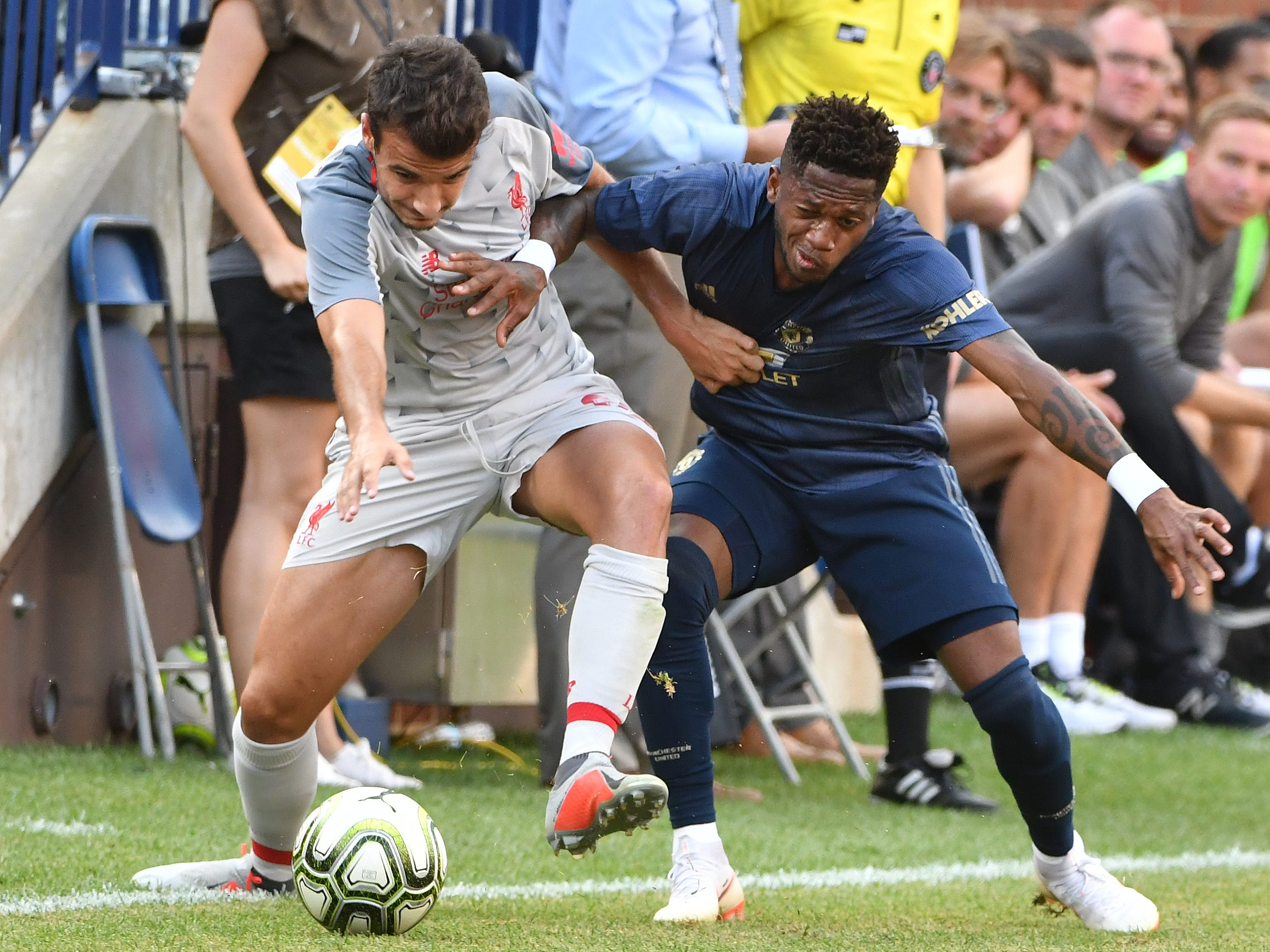 Liverpool's Pedro Chirivella and Manchester's Anthony Martial mix it up chasing a ball down the sidline in the second half.