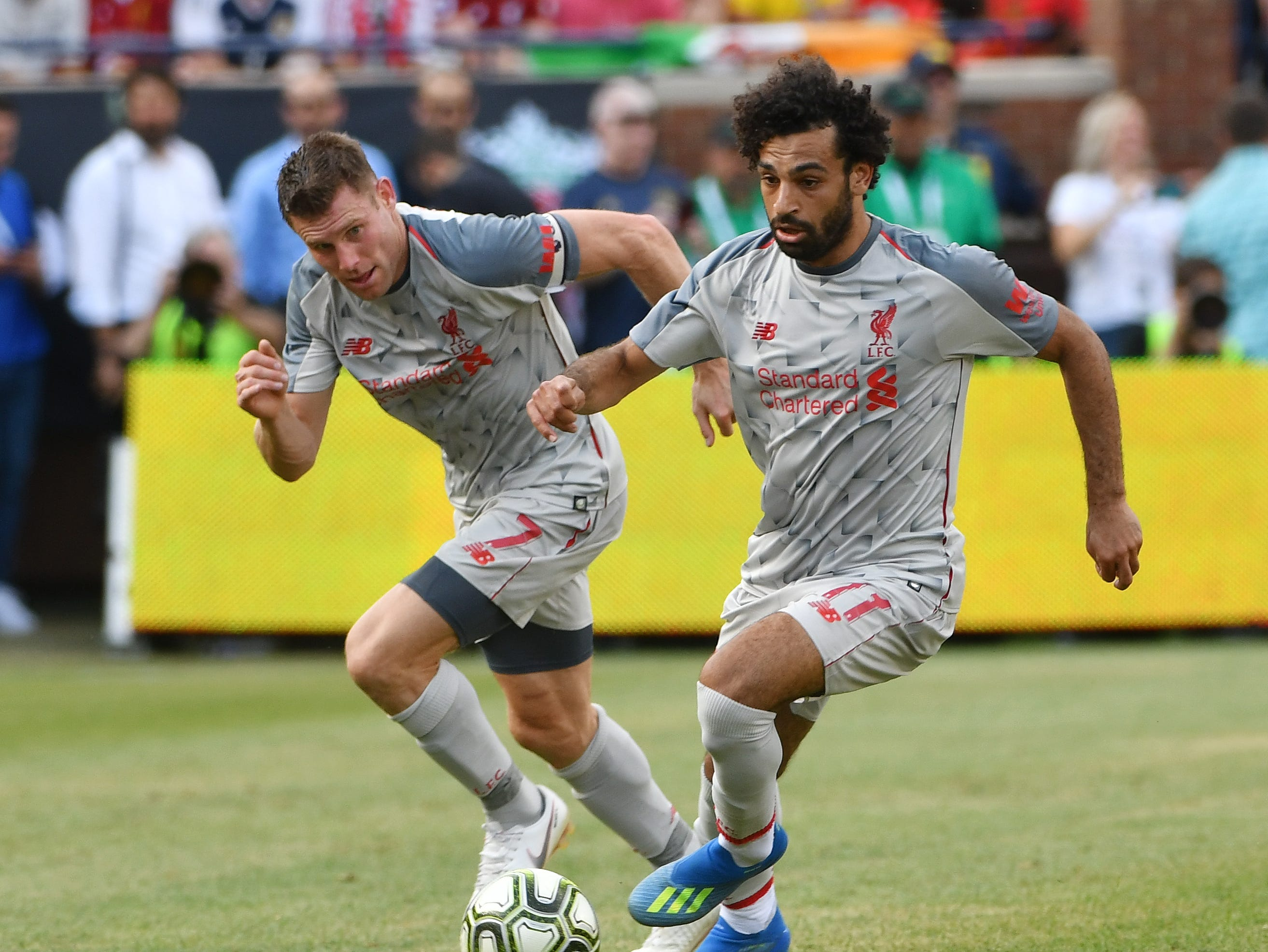 Liverpool's James Milner and Mohamed Salah bring the ball up field in the first half.  I