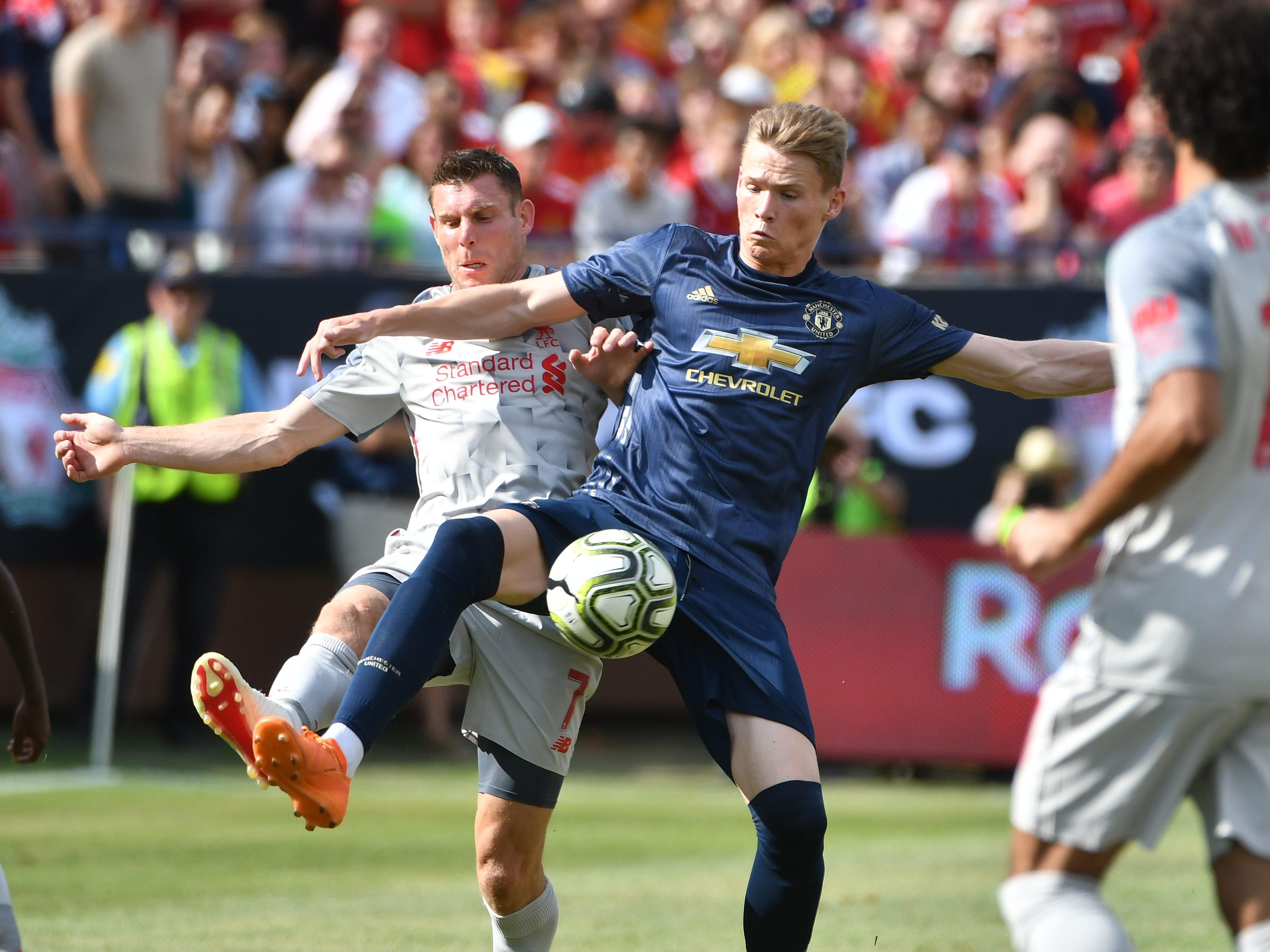 Liverpool's James Milner and Manchester's Scott McTominay battle over a ball in the first half.