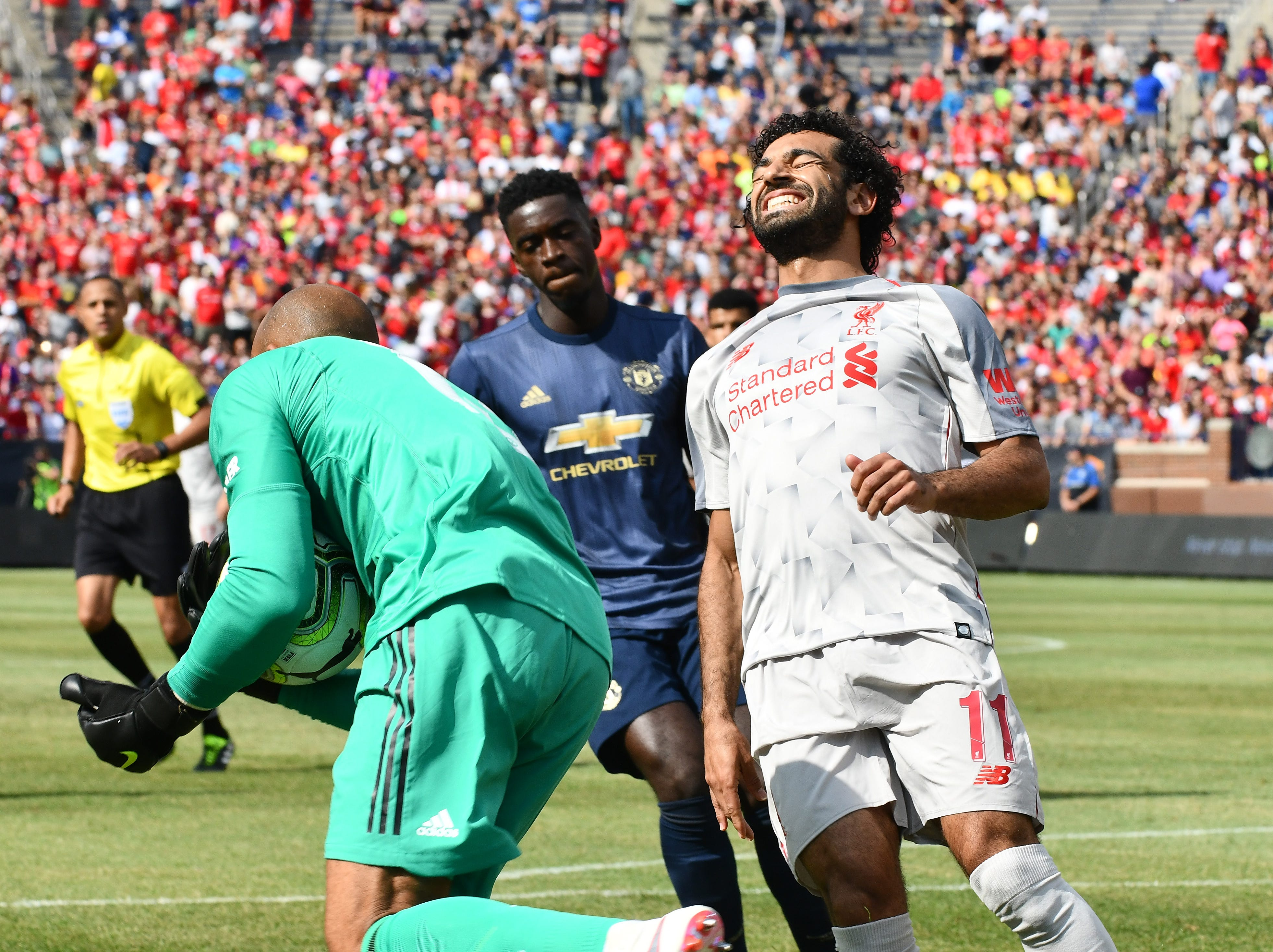 Liverpool's Mohamed Slah grimaces as Manchester goalie Lee Grant is able to scoop up a ball in front of the net before Slah could get a foot on it in the first half.