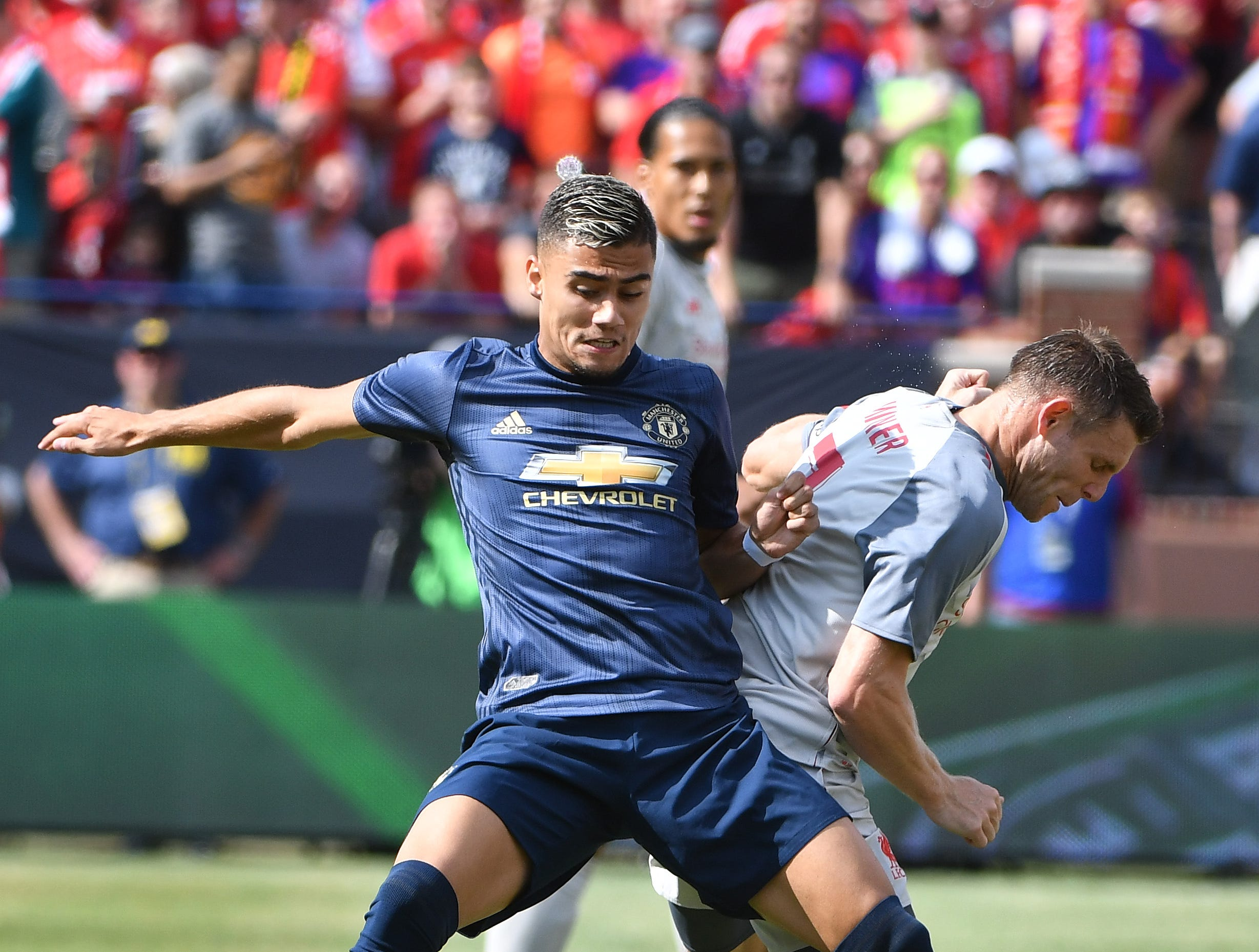 Manchester's Andreas Pereira and Liverpool's James Milner battle for the ball in the first half.