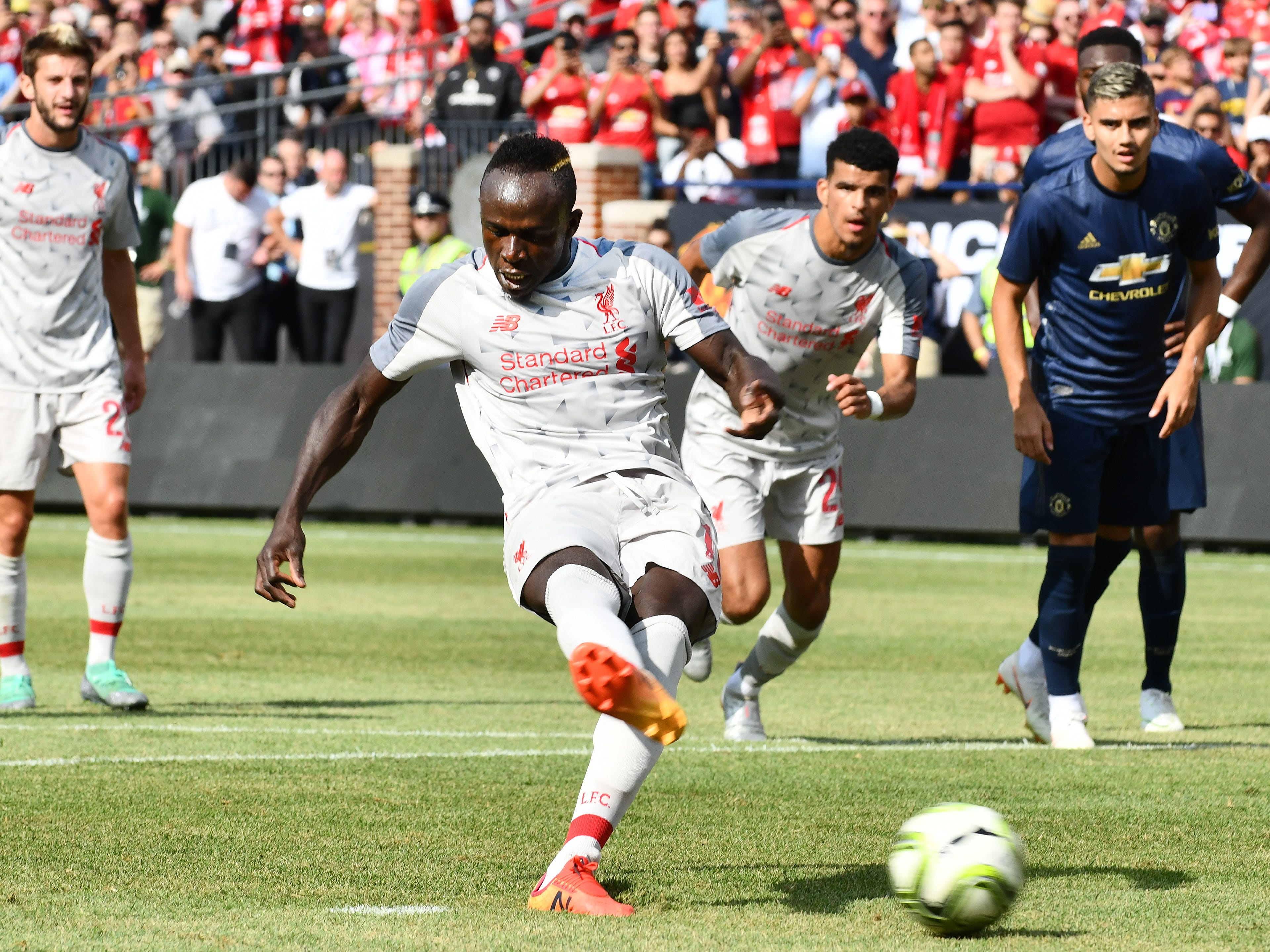 Liverpool's Said Mane' puts in a penalty shot for the first goal of the game in the first half.